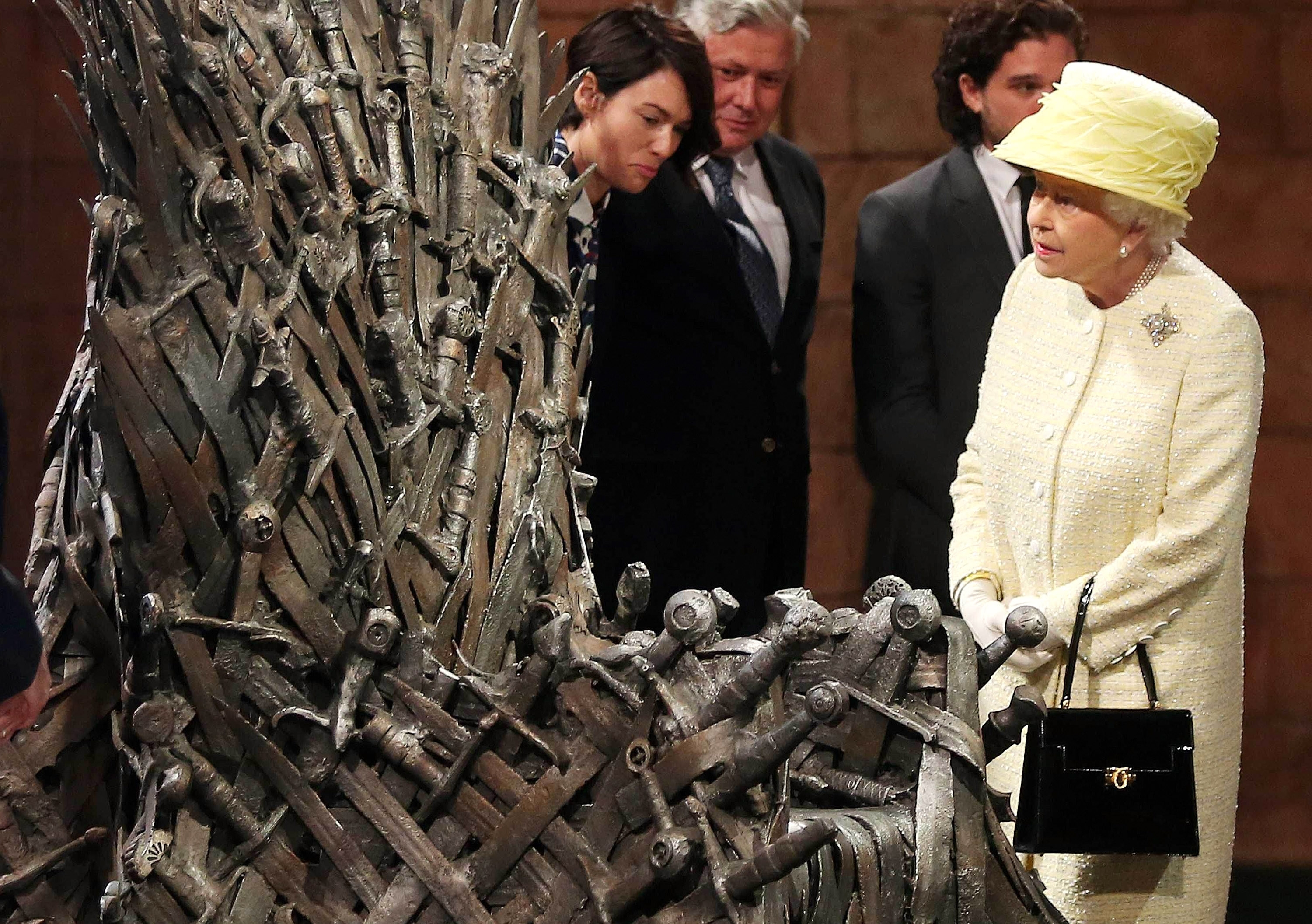 """Queen Elizabeth II meets cast members of the HBO series """"Game of Thrones"""" as she views the Iron Throne on the set of the show Tuesday in Belfast, Northern Ireland."""