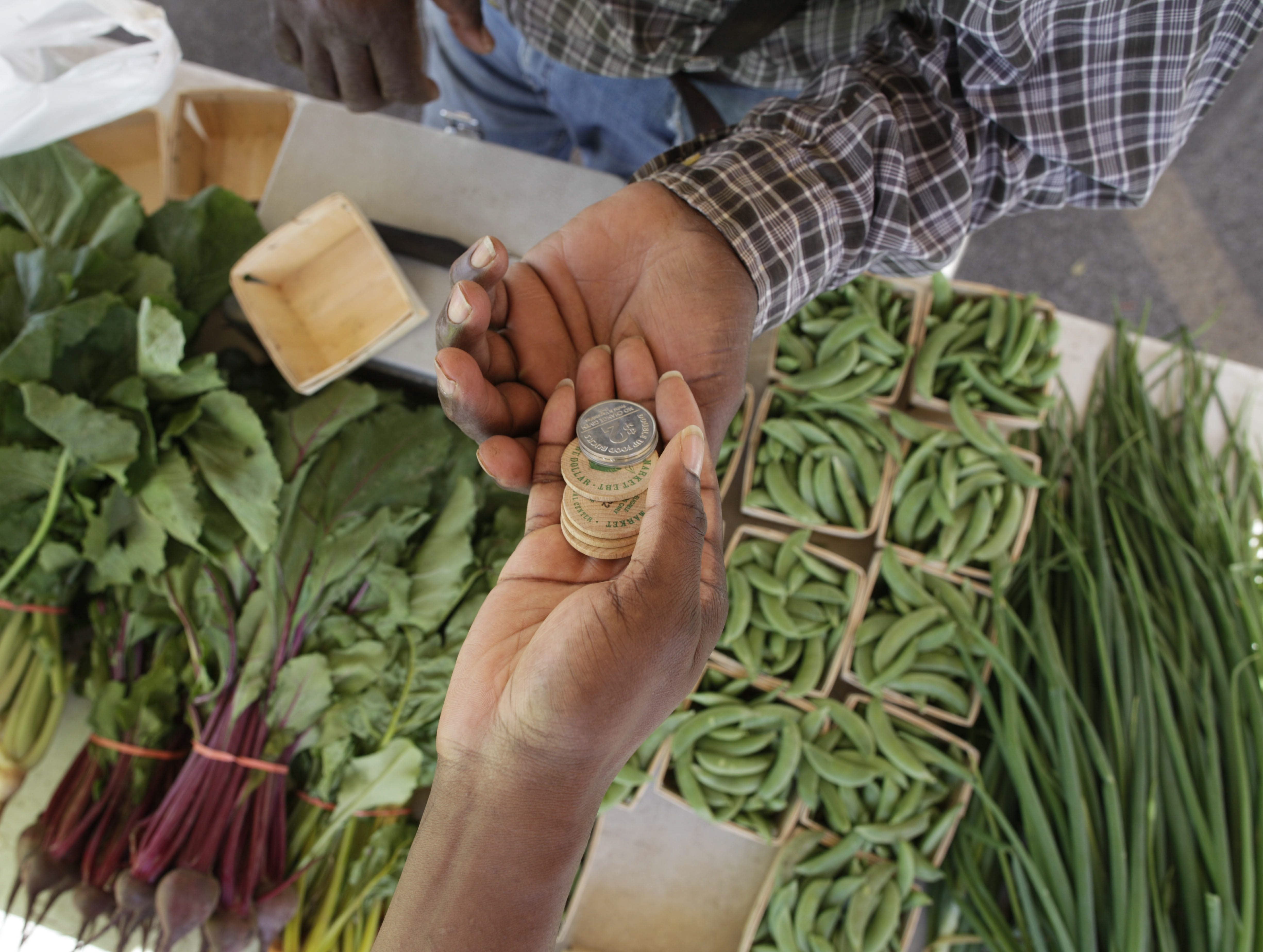 """A customer uses ECMC Farmers' Market currency tokens and """"Double Up Food Bucks,"""" two-dollar coins given to shoppers using their state benefit cards to purchase produce."""