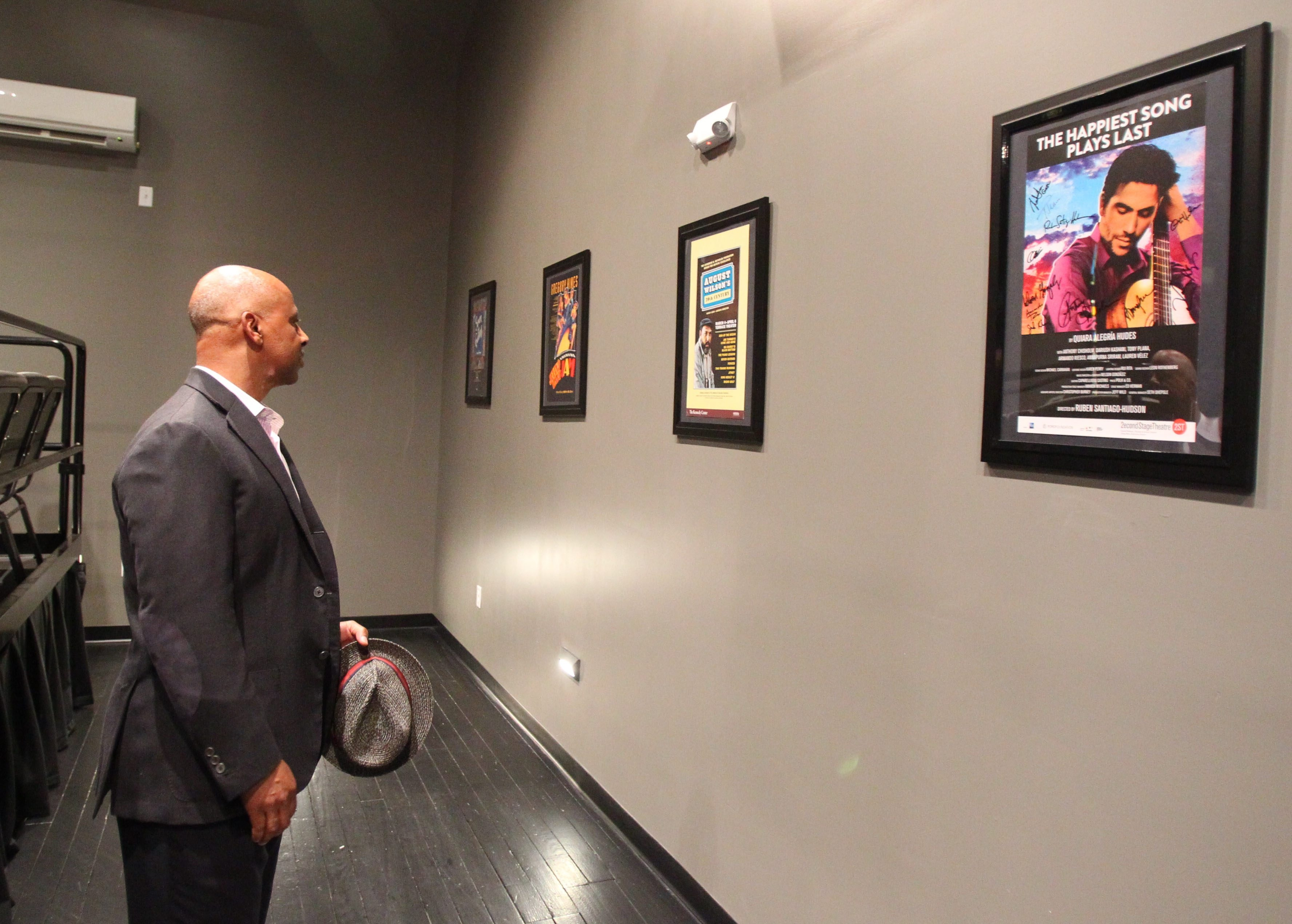 Actor Ruben Santiago-Hudson looks at the posters he donated to the new Ruben Santiago-Hudson Fine Arts Learning Center, part of Global Concepts Charter School in Lackawanna, on Sunday.