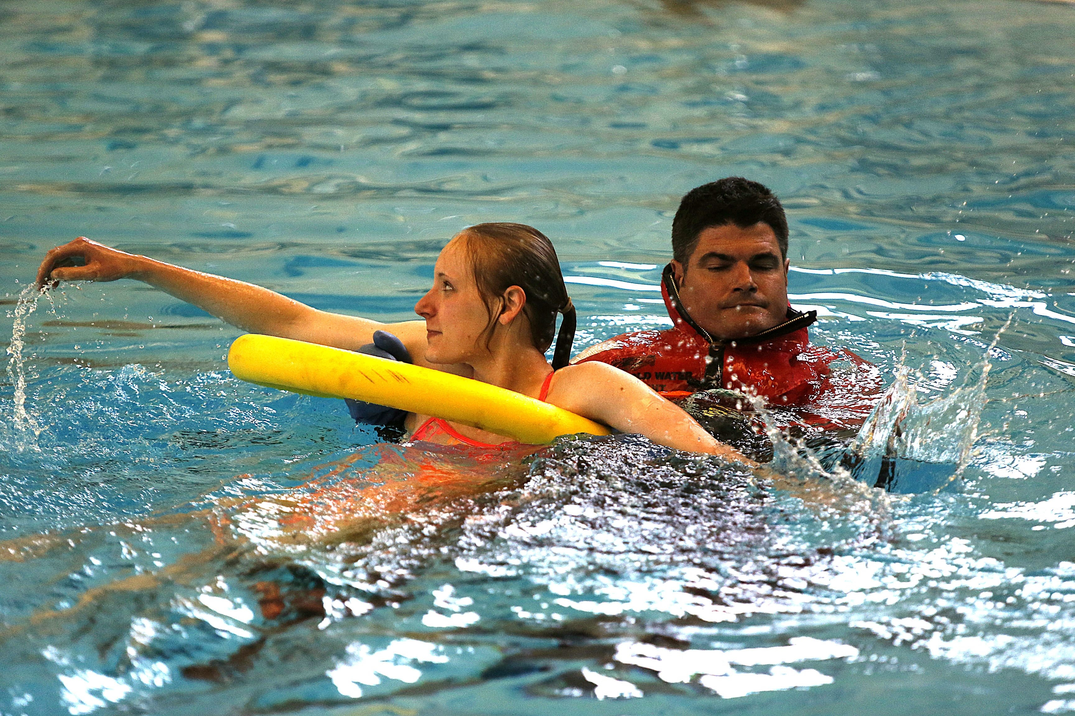 Buffalo firefighter Kevin Lynch simulates a water rescue with volunteer Danielle Polniak in the City Honors School pool on Saturday as part of a festival organized by Buffalo City Swim Racers.