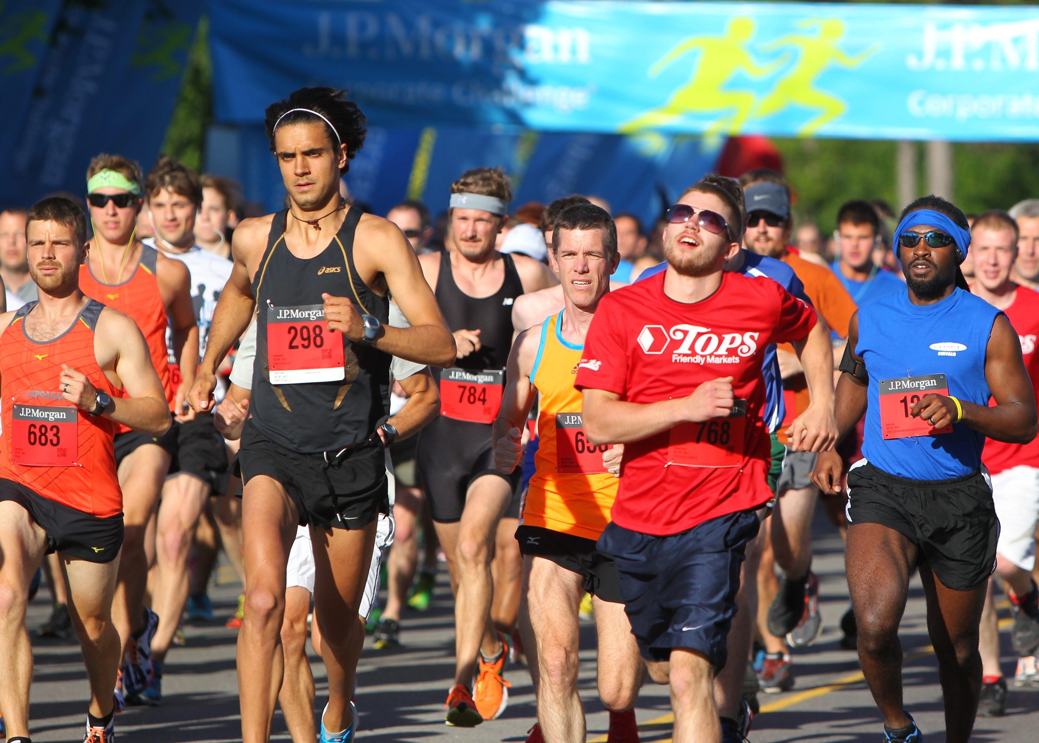 Men's winner Vasilis Kariolis, left in black, and other runners takes the start during the J.P. Morgan Corporate Challenge in Delaware Park in Buffalo on June 19.