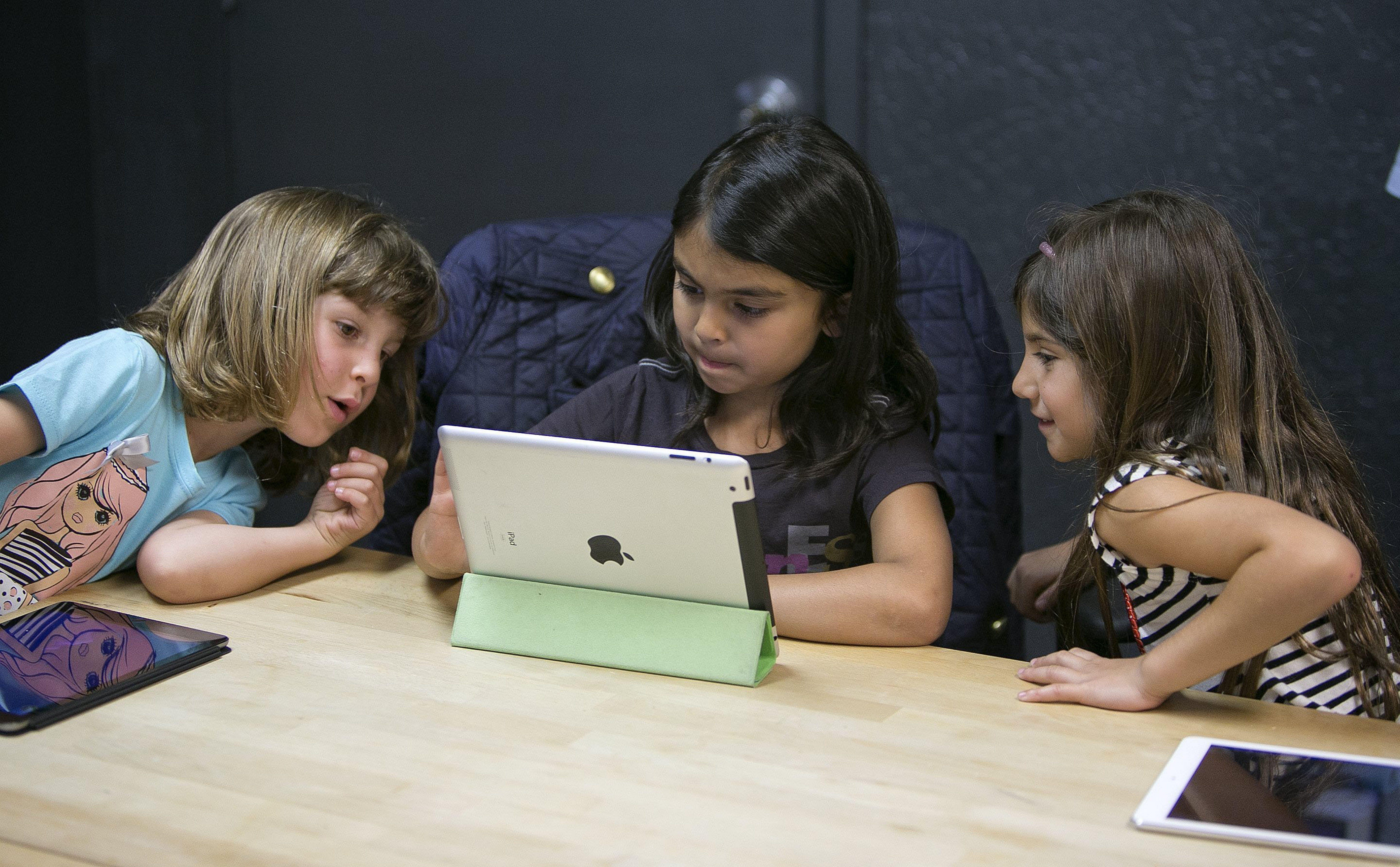 Anna Heath, 5, from left, Aryka Gunsagar, 6, and Rayah Ghosheh, 6, test Kidaptive's Leo's Pad app at the Kidaptive office in Palo Alto, Calif.