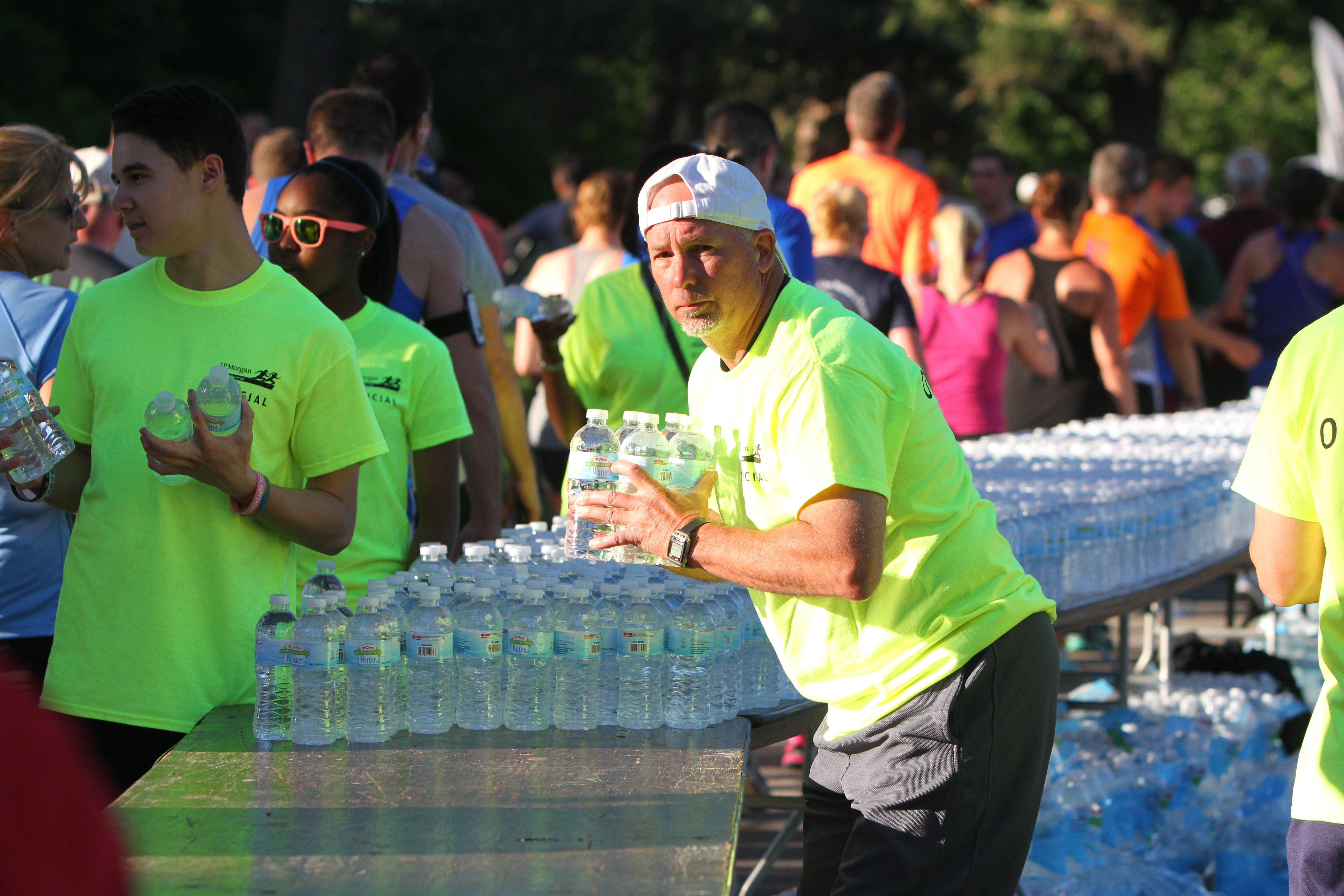 Volunteers pass out water to runners at the finish line during the J.P. Morgan Corporate Challenge.