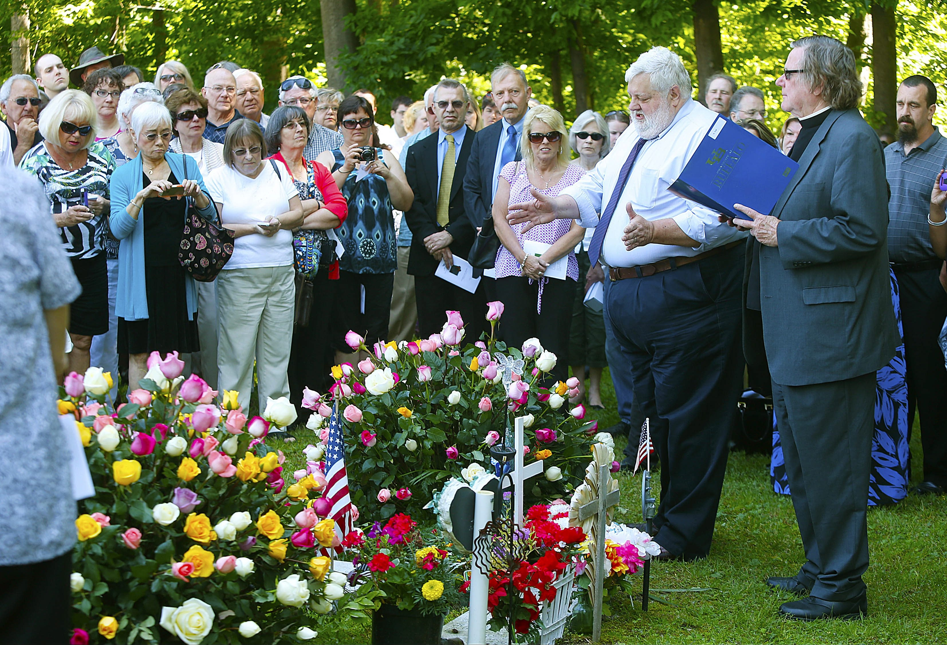 Monsignor Patrick Kelcher, right, and Raymond Dannenhoffer, second from right, director of the UB Anatomical Gift program, deliver a closing prayer. Family members during a memorial service honoring those that donated anatomical gifts to UB medical school.  This was at the Skinnerville Cemetery at UB north onThursday, June 19, 2014.  (Robert Kirkham/Buffalo News)