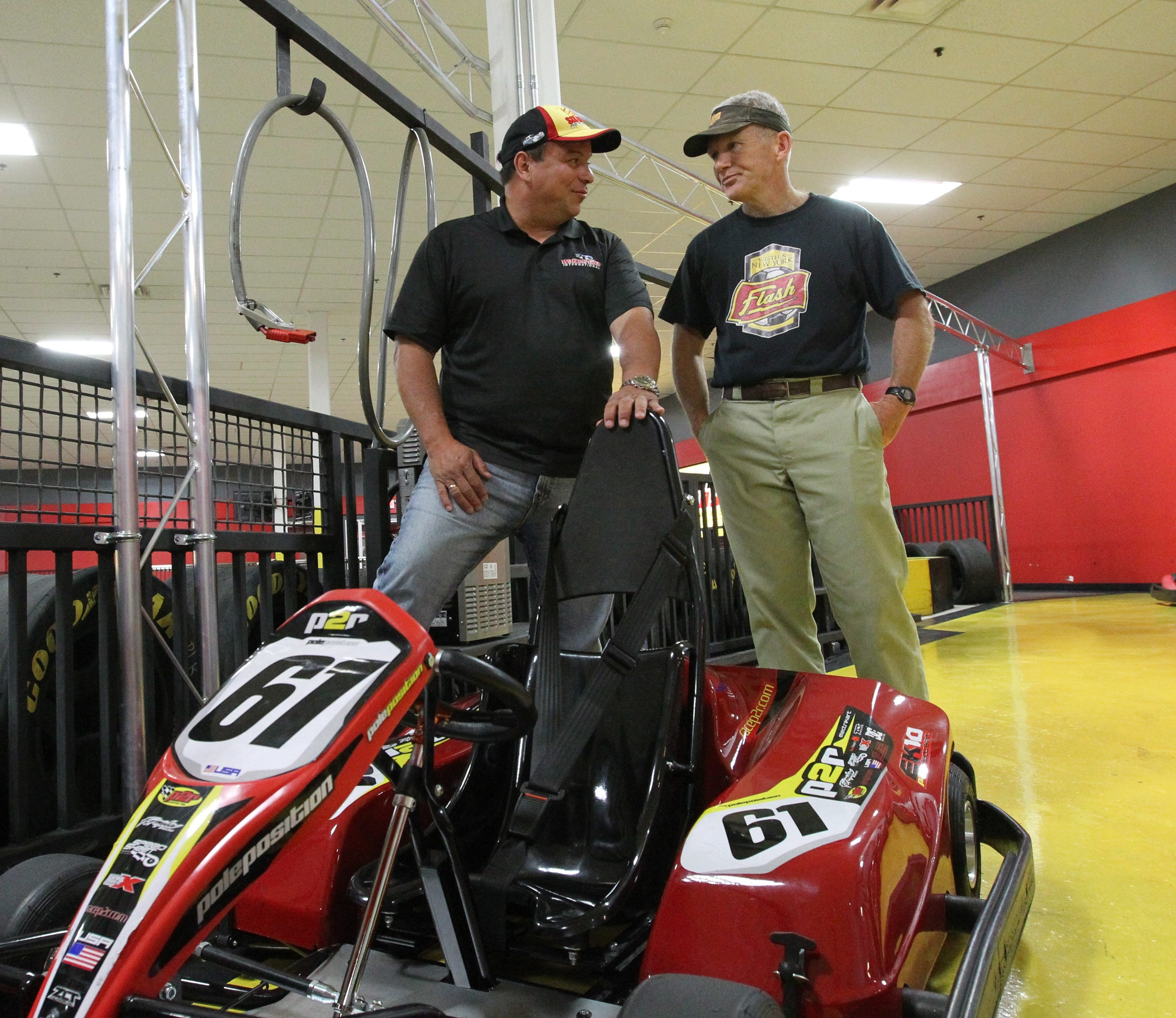 Watkins Glen president Michael Printup, left, talks to Joe Sahlen about racing during an event at the Pole Position Raceway at Walden Galleria this week.
