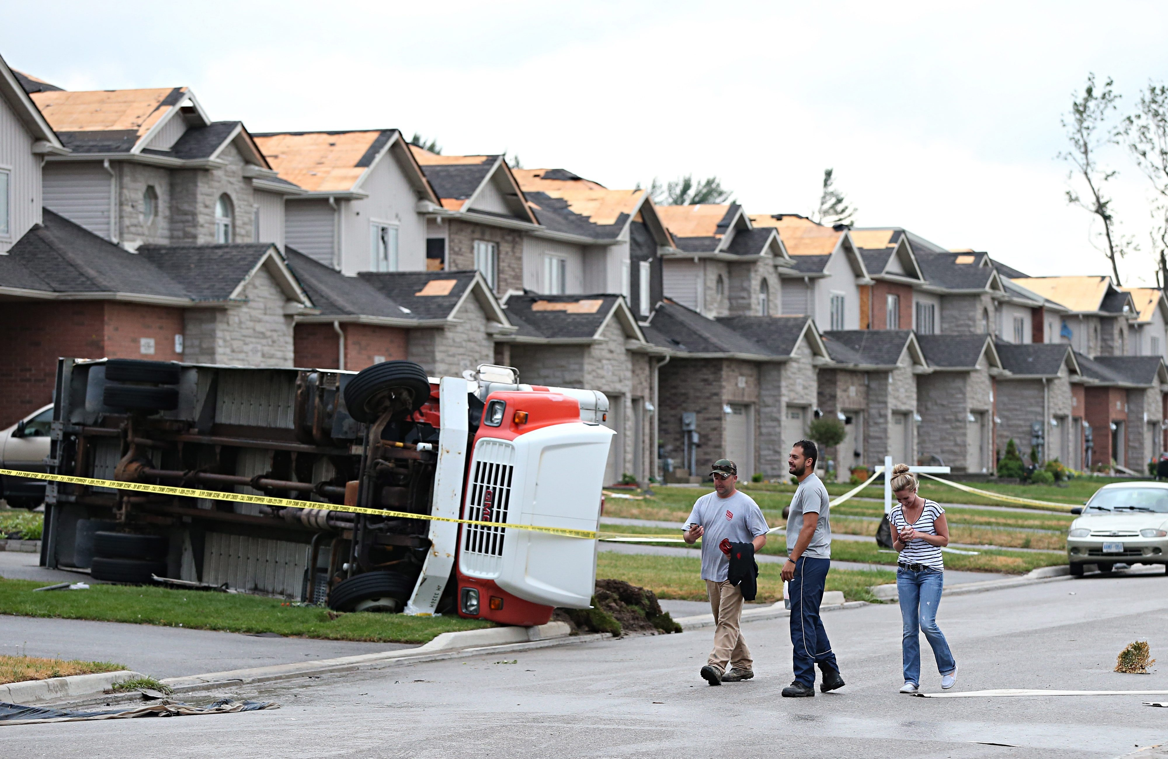 Residents observe the damage on a street following a storm in Angus, Ontario, on Tuesday, June 17, 2014. Provincial police say there are reports of some minor injuries after severe weather ripped through the central Ontario community. (AP Photo/The Canadian Press, Peter Turchet)