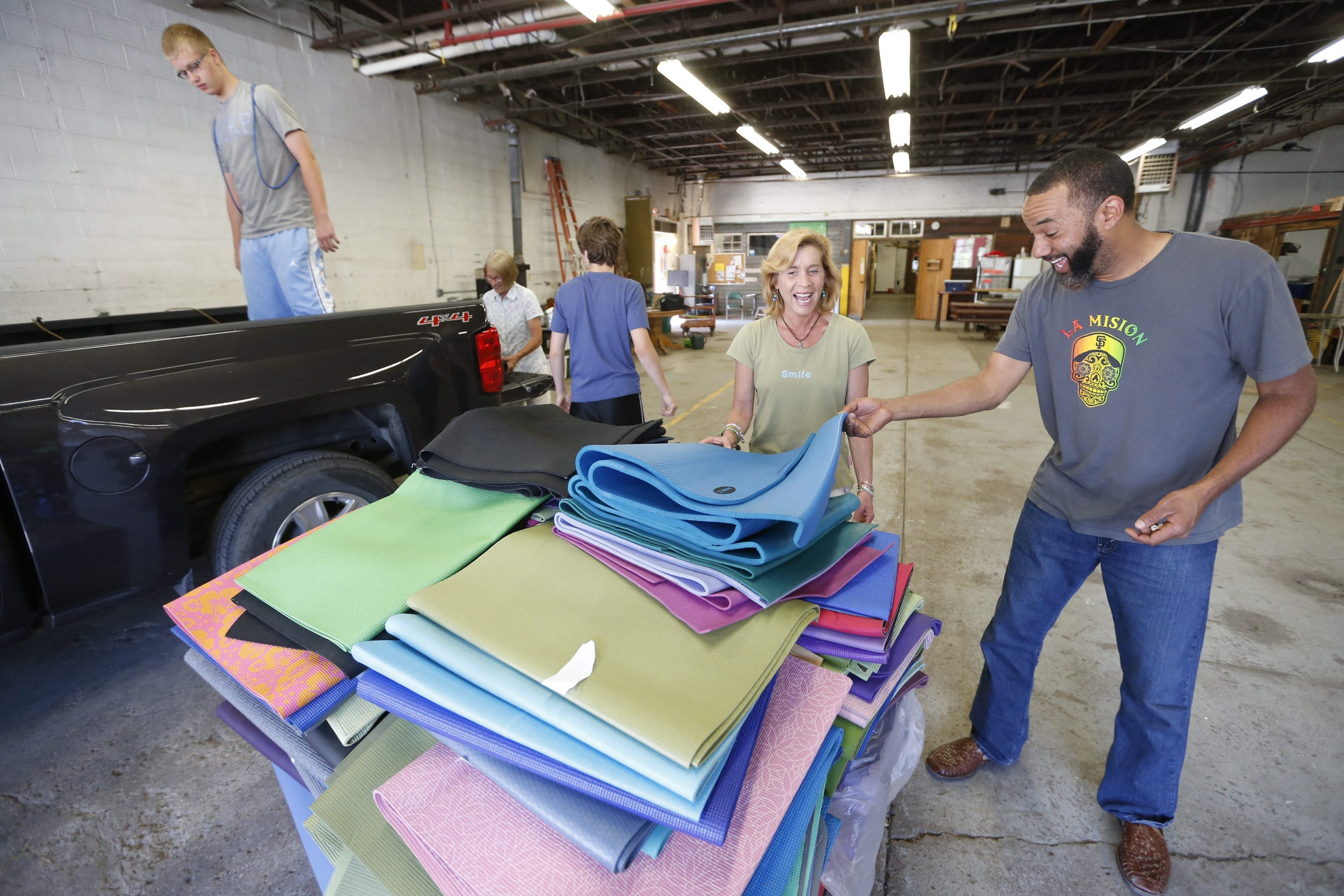 Jason Ross Brown, right, delivered 200 donated yoga mats to Mary Jo Gervase, second from left, at the Foundry on Northampton on Sunday. Gervase will distribute the mats to Buffalo schools.