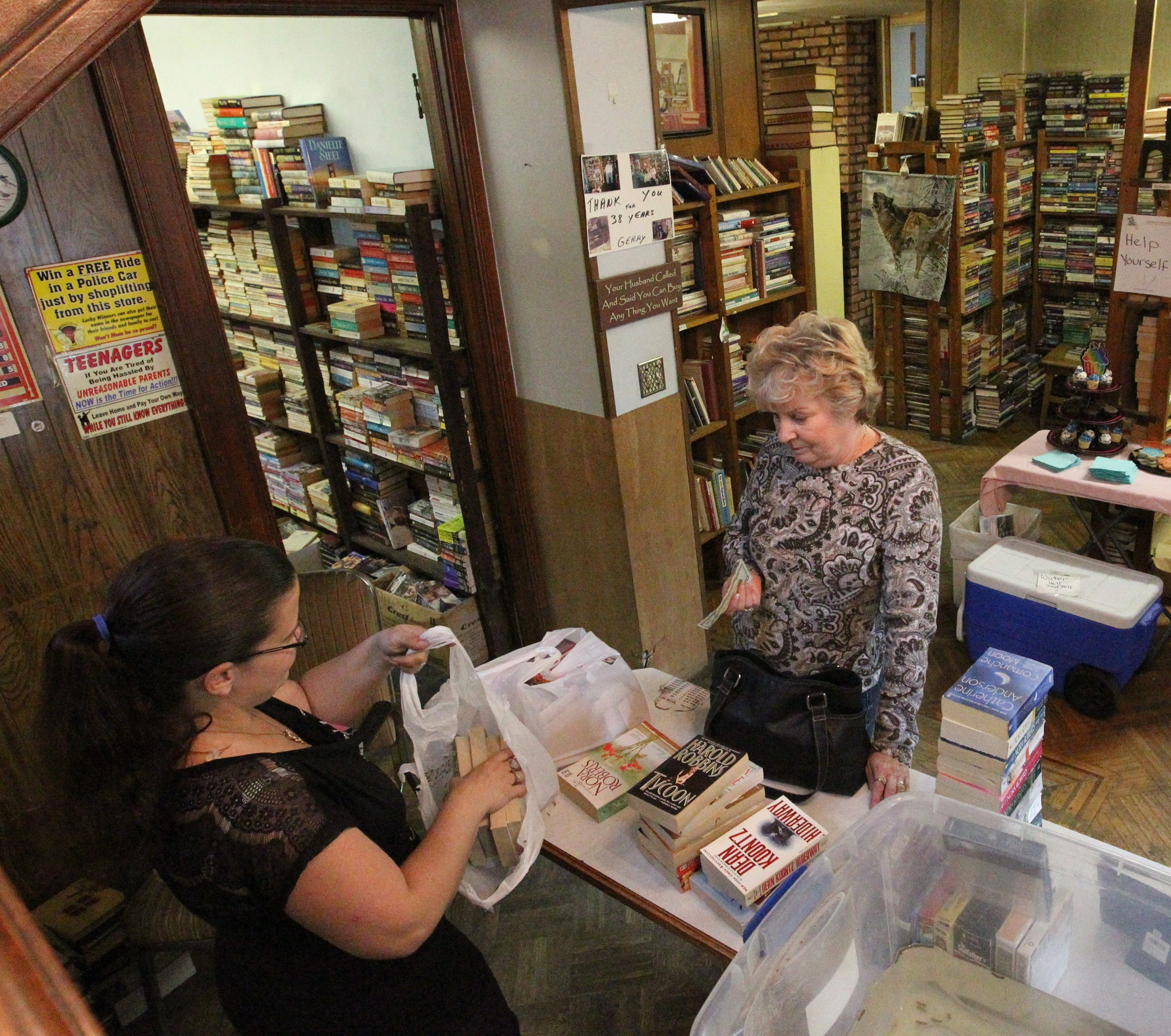 Valerie Savage of Buffalo buys books from  Dee Dee Schneider at the Paperback trading post on 2292 Seneca Street in Buffalo,NY on Saturday, June 14, 2014.  (James P. McCoy/ Buffalo News) Dee Dee Schneider