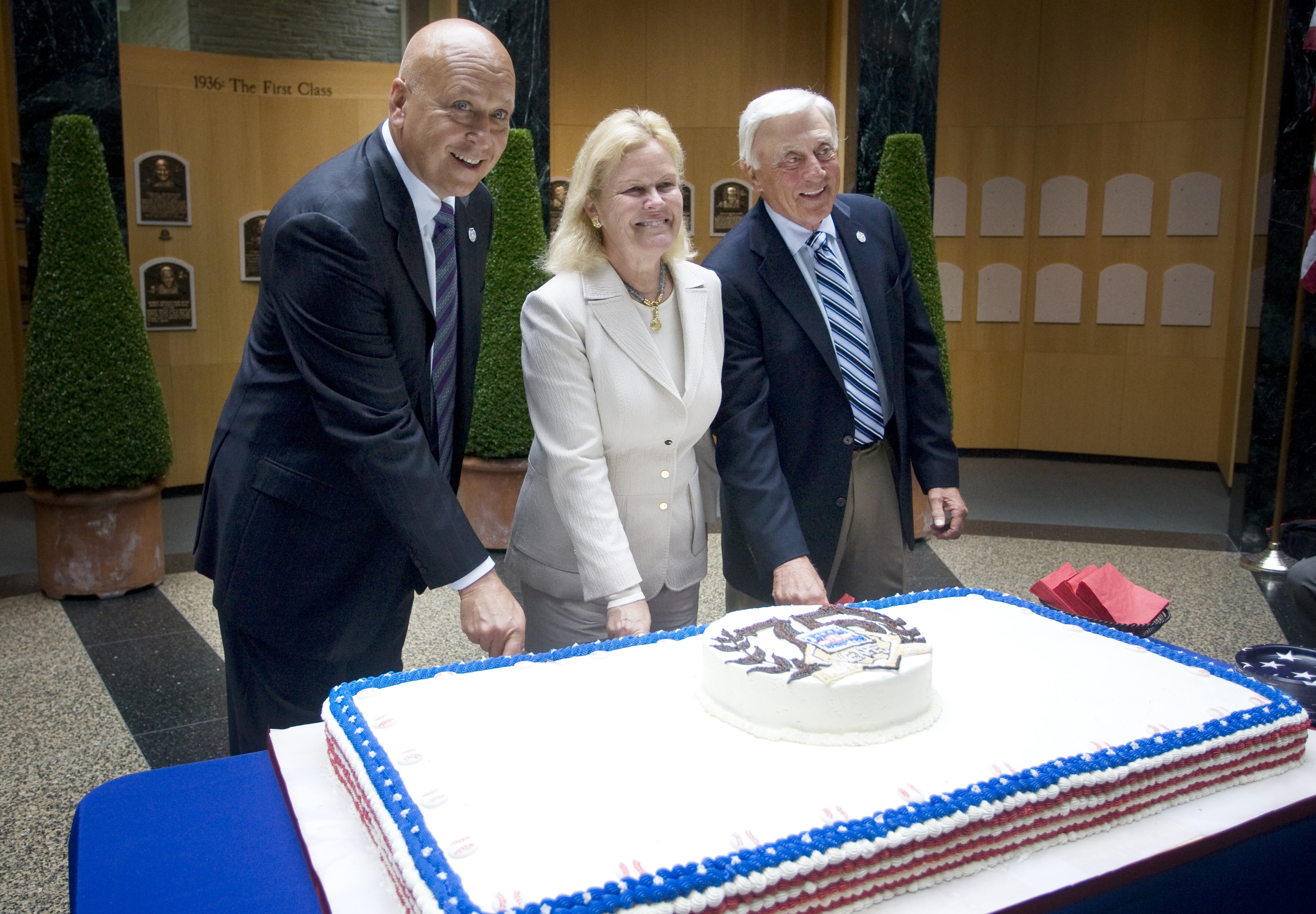 Cal Ripken Jr., left, and Phil Niekro, right, along with Jane Forbes Clark, chairwoman of the board of directors of the National Baseball Hall of Fame and Museum, celebrate the museum's 75th Anniversary.