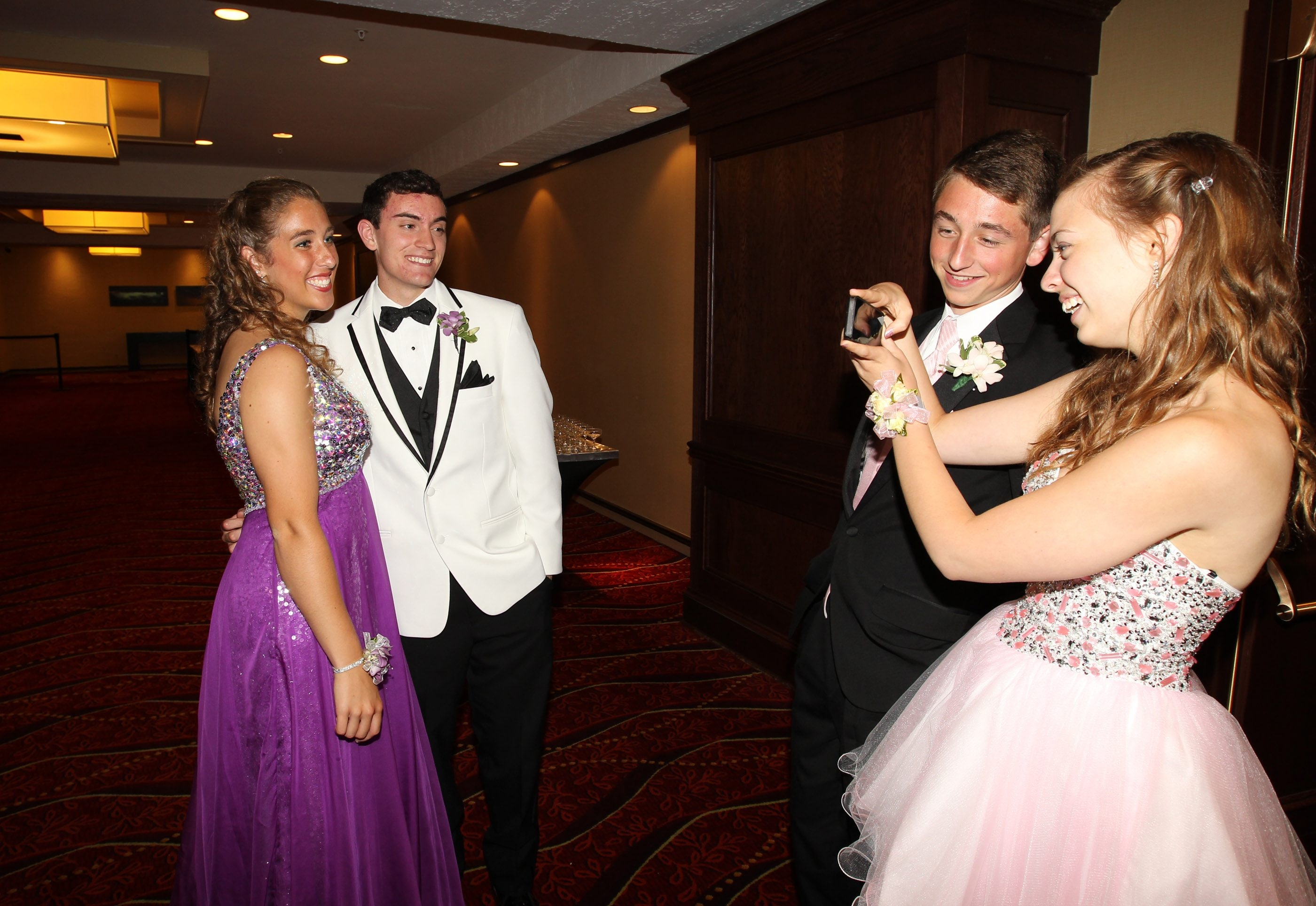 Katrina Buczkowski and Skyler Reinhardt  have their photo taken by Emily Schupbach and Alex Tryjankowski. They were enjoying their senior  prom before she had to leave early to travel to Glens Falls  for today's state softball championship at 9 a.m.