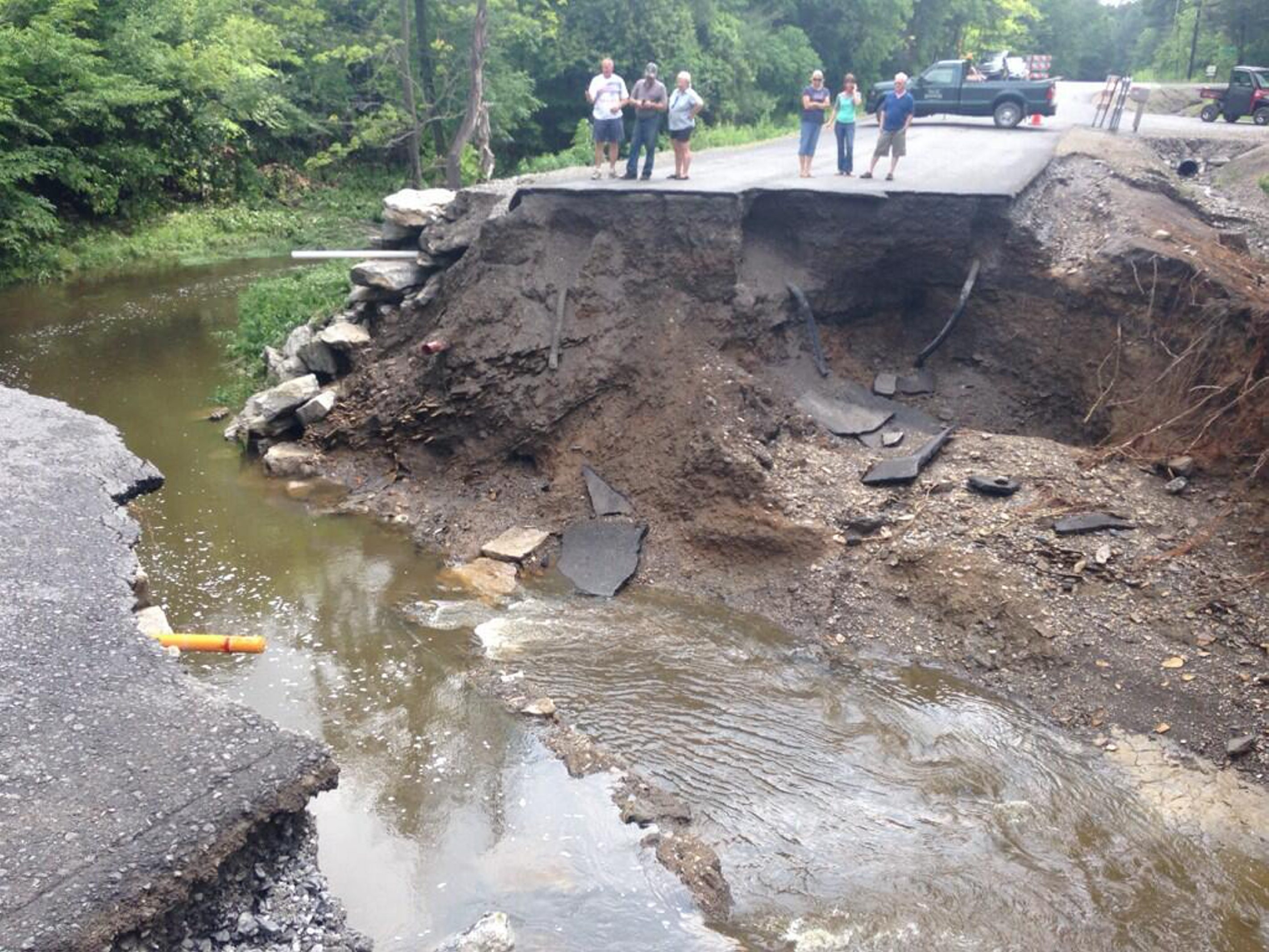 Residents stand at the edge of a washed-out road at the border of Erie and Wyoming counties today. (Mark Mulville/Buffalo News)