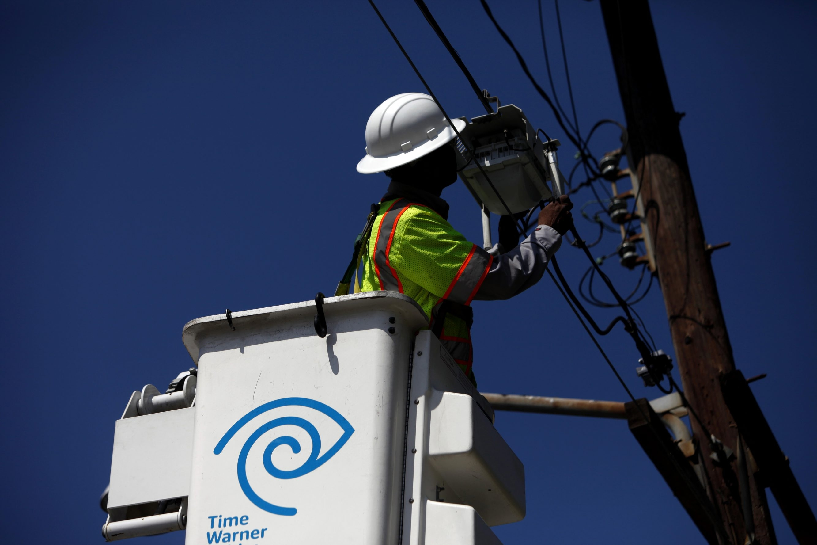 A technician for Time Warner checks the connection for a WiFi hotspot in Manhattan Beach, Calif.