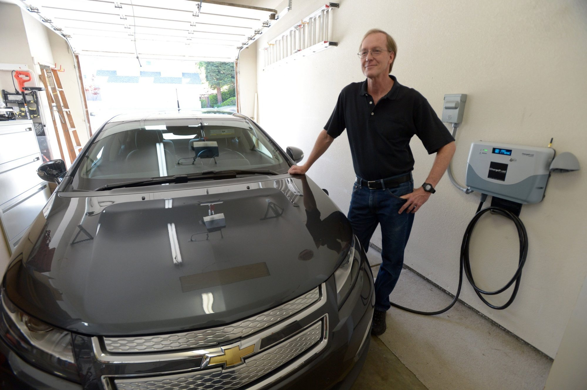 Randy Ross, an electrical engineer, stands near the plugged-in Chevy Volt he uses to commute from his Pleasanton, Calif., home. Ross also has a battery-based energy storage device, mounted on the wall of his garage, that is part of a pilot project from SolarCity. He currently pays just $1 a year for the battery system.