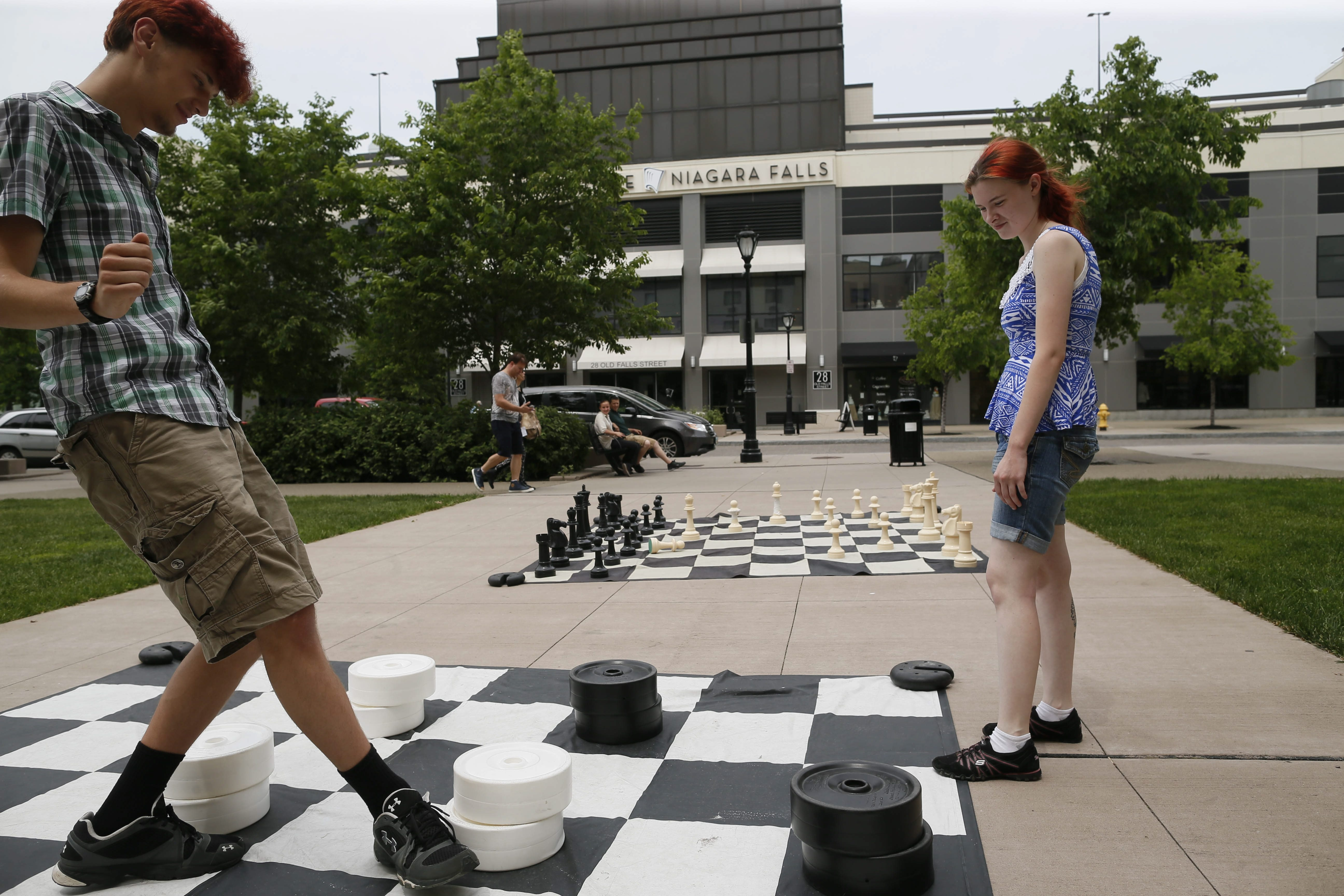 Kevin Sandmaier and Jayme Rothenberger of Buffalo play checkers on a giant board on Old Falls Street, one of the many fun activities this summer in Niagara Falls.