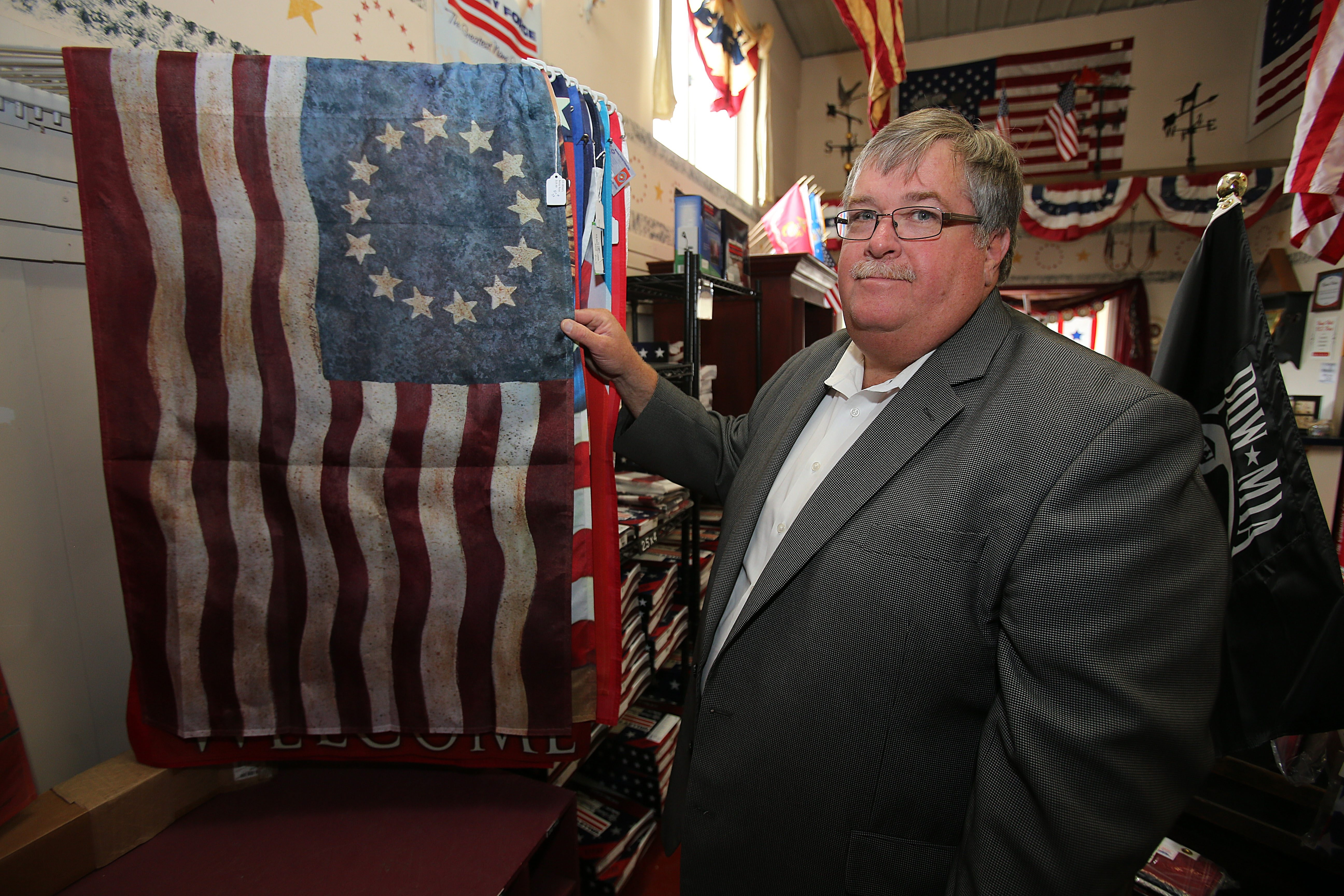 John Cooper Sr., owner of Cooper Sign Co. and Old Glory Flags, poses with a period flag at his company's Niagara Falls offices.