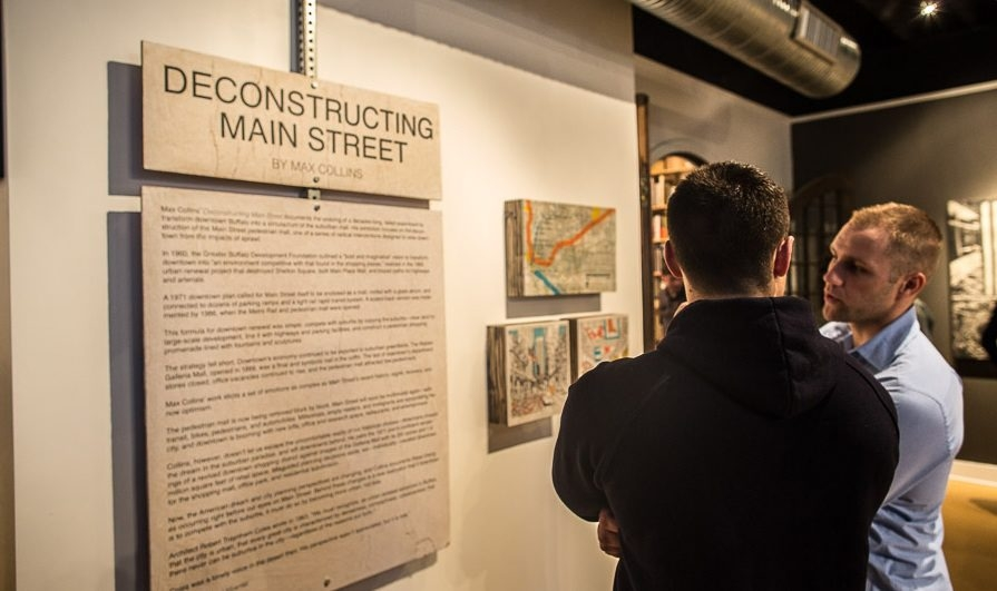 """Attendees at Max Collins' exhibition opening of """"Deconstructing Main Street"""" read his introductory text. (Chuck Alaimo/Special to the News)"""