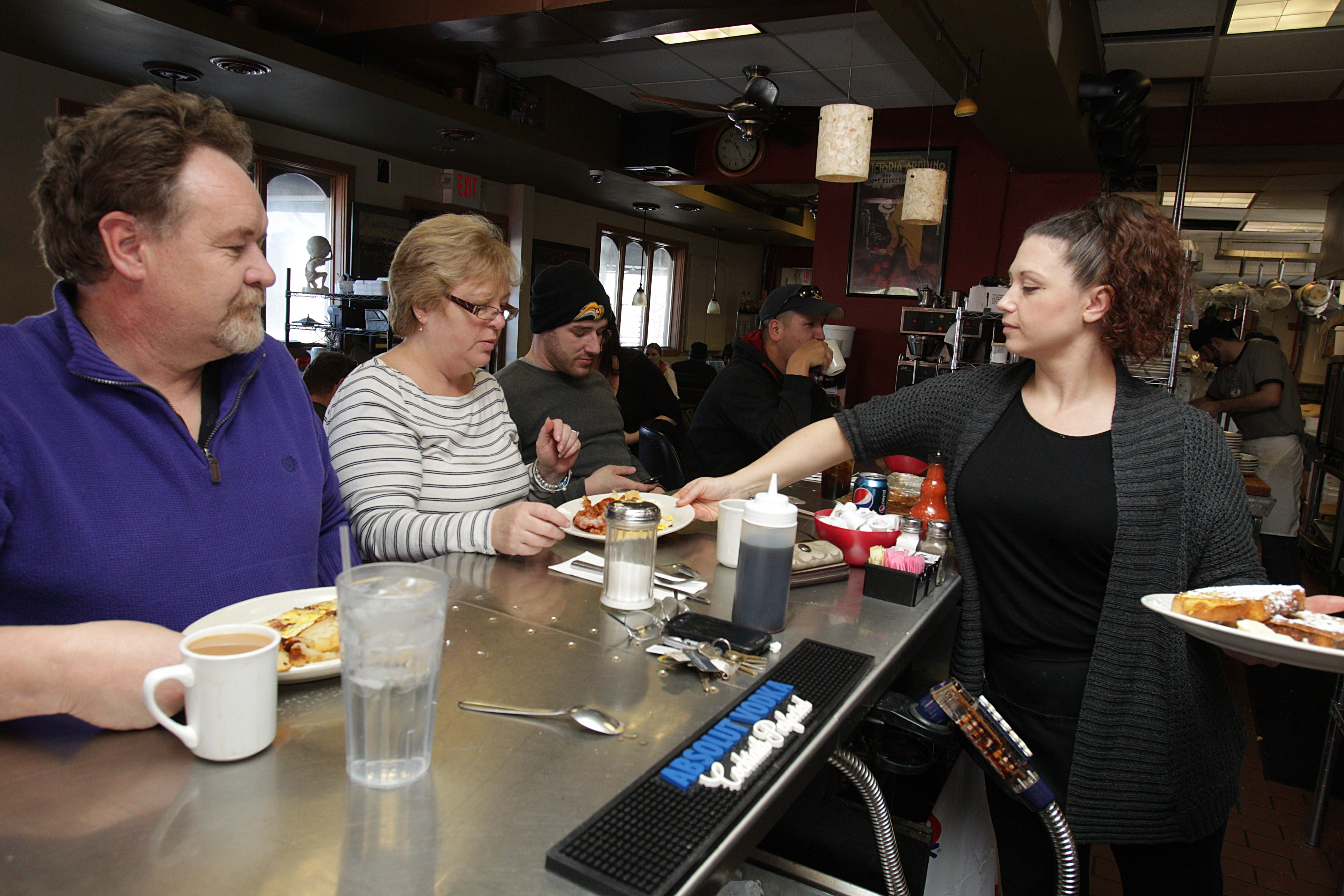 Adrienne Byrnes right, serves breakfast to regular customers Joe, left, and Janet Walsh of Buffalo and their son Joe in Sophia's Restaurant.