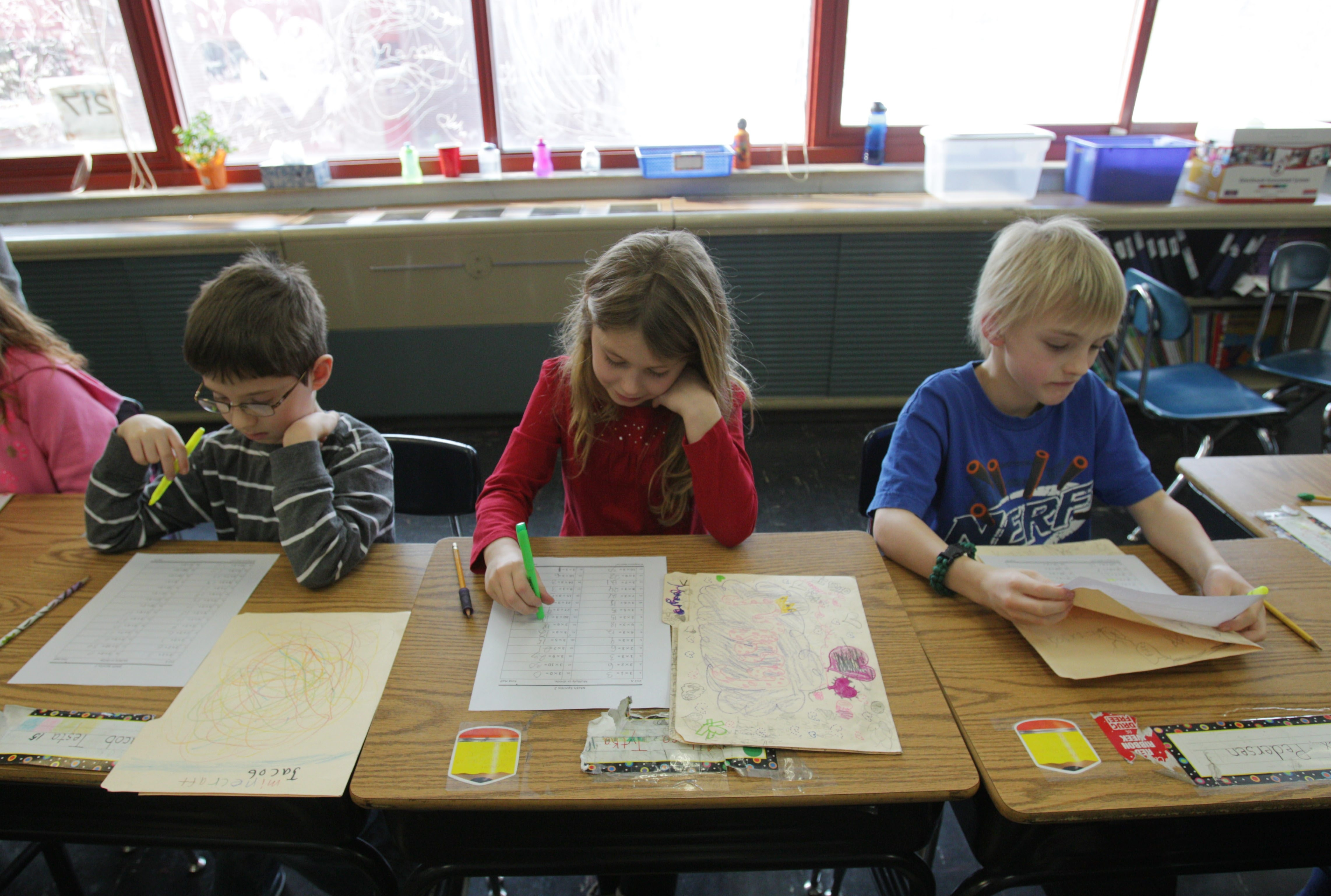 At Smallwood Elementary, Joanne Carroll's third- grade class does math sprints. They complete as many multiplication and division problems as they can in one minute. They all correct together afterward.  From left are Jacob Testa, Meliisa Tyka and Alex Pederson.