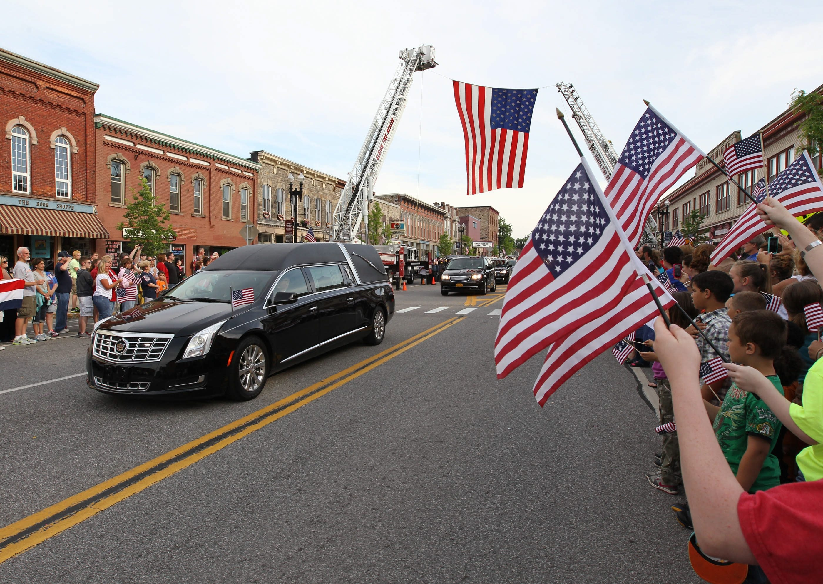 James P. McCoy/Buffalo News   The funeral procession for Army Sgt. Shaina Schmigel travels through Medina as residents line the streets to pay their respects.