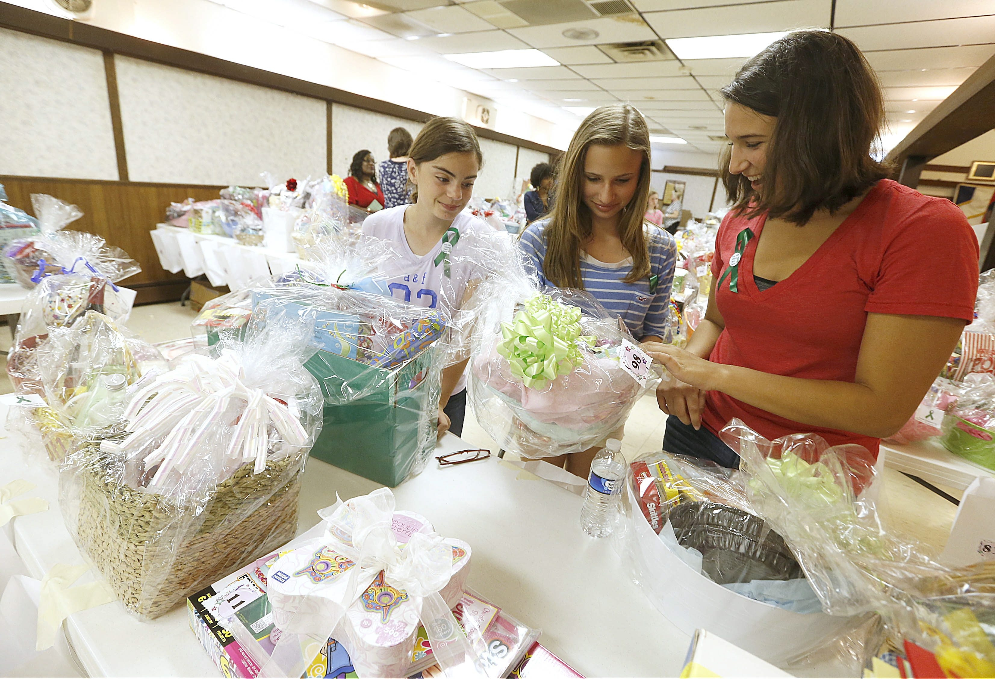 Maddy Moran, Anna Mucha and Julia Dipasquale look at raffle items at VFW Post 8113 during a benefit opposing the relocation of the Western New York Children's Psychiatric Center on Sunday.