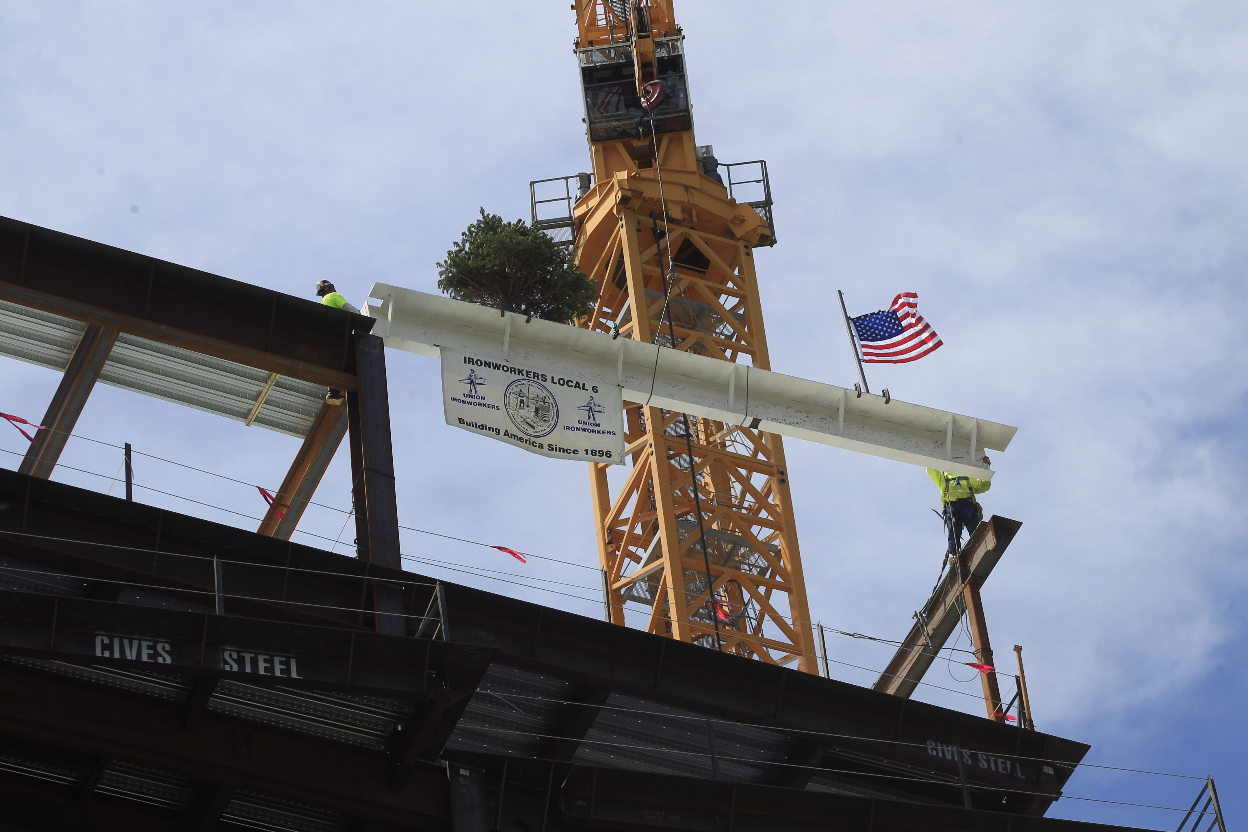 Ironworkers get ready to wrangle the final steel beam onto the new 11-story Roswell Park Clinical Sciences Center after it is hoisted into place  on Friday.  See a photo gallery at BuffaloNews.com.