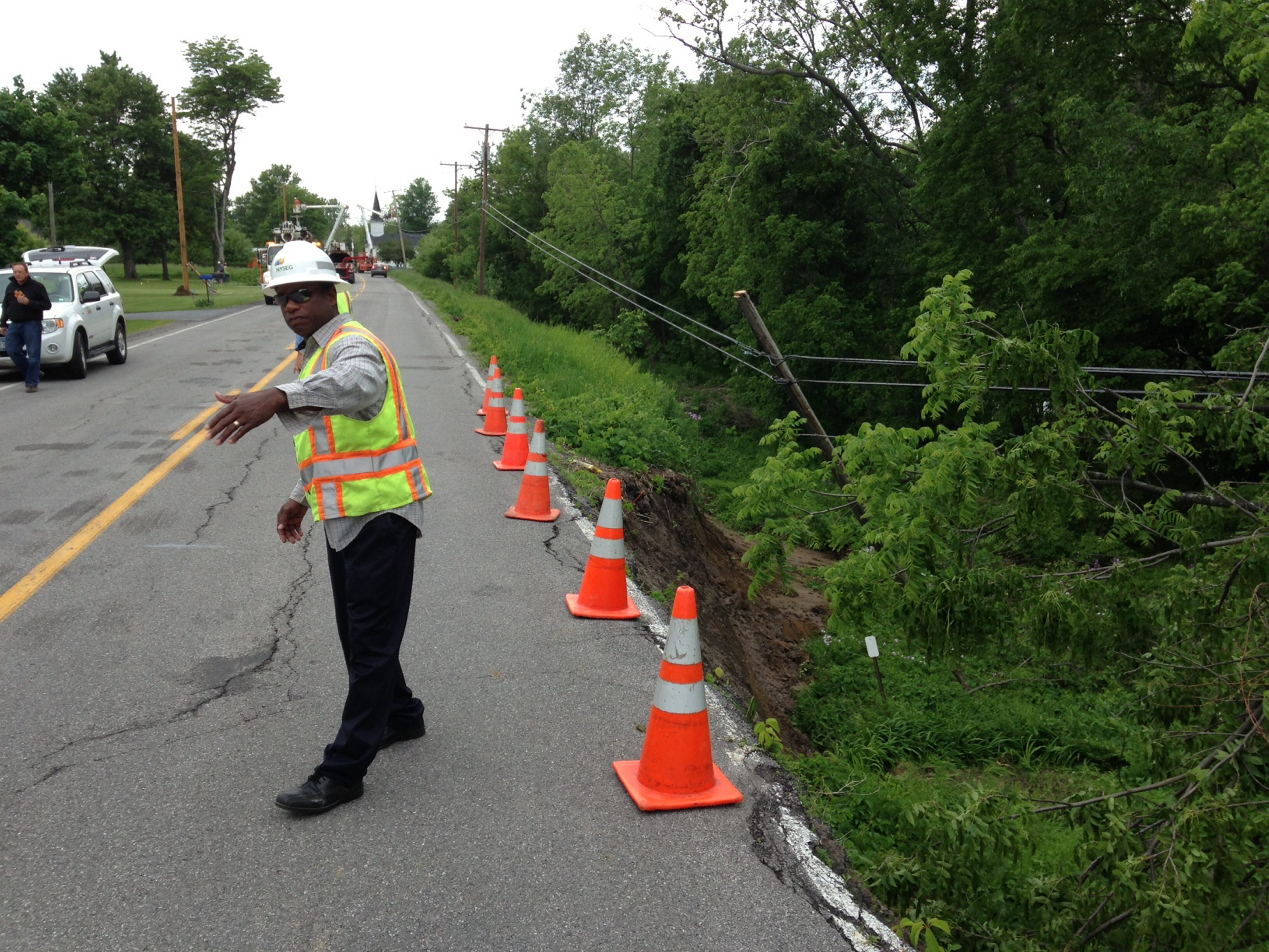 Ron Lewis from NYSEG directs traffic along Tonawanda Creek Road as repairs related to the bank slide, seen at right, took place.