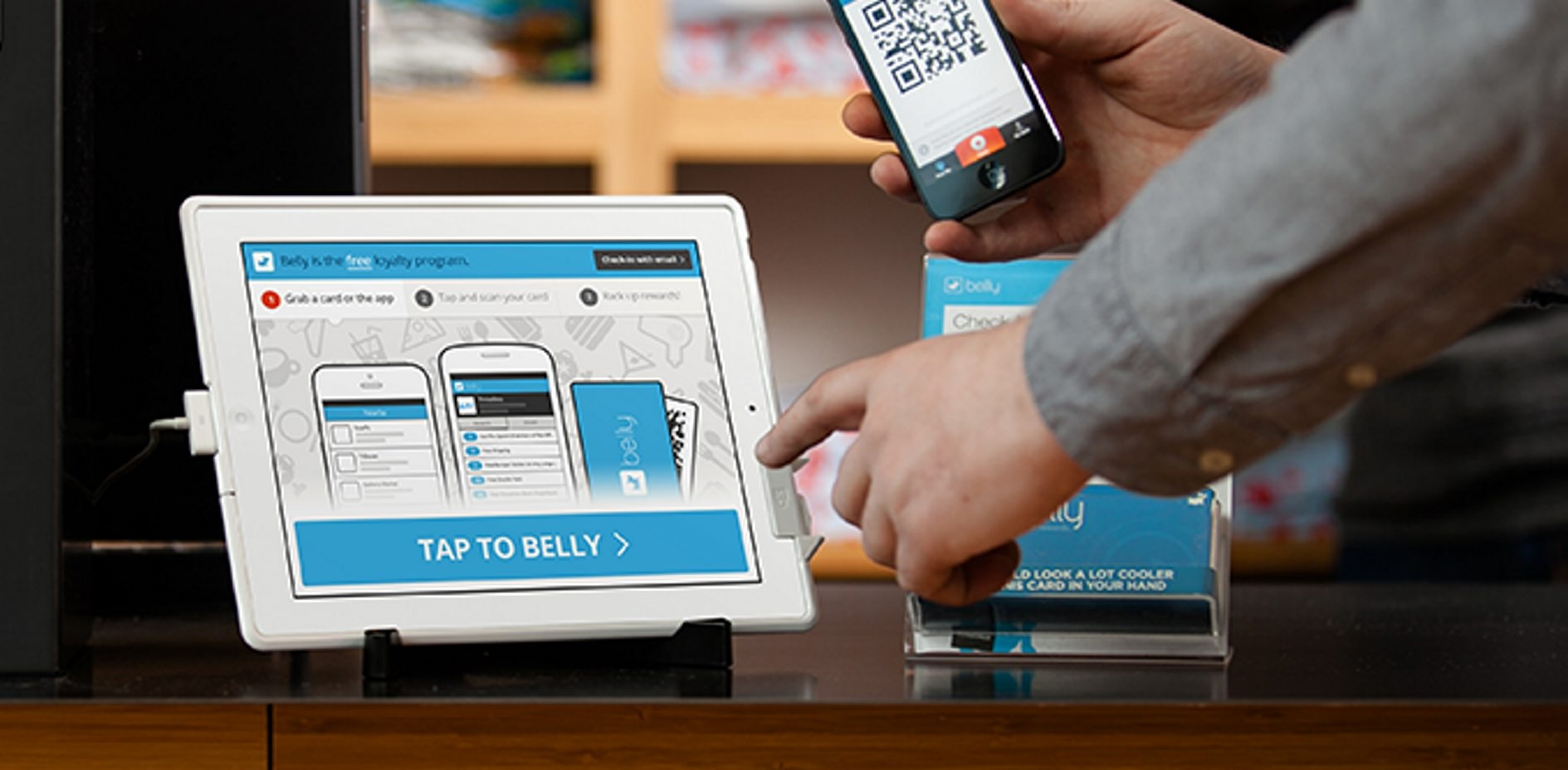 Tap to belly. A customer uses the belly rewards iPad program, compatible with smartphone or key fob.
