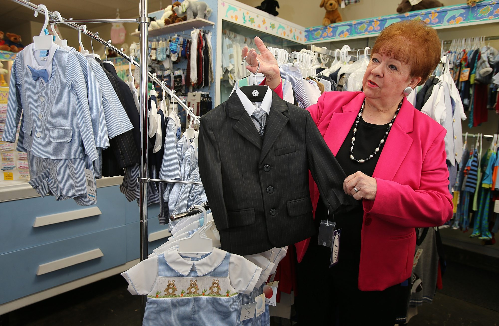 Joanne Shaghoian shows off  merchandise in her Village of Lewiston store, Sister and Brother Children's Apparel.