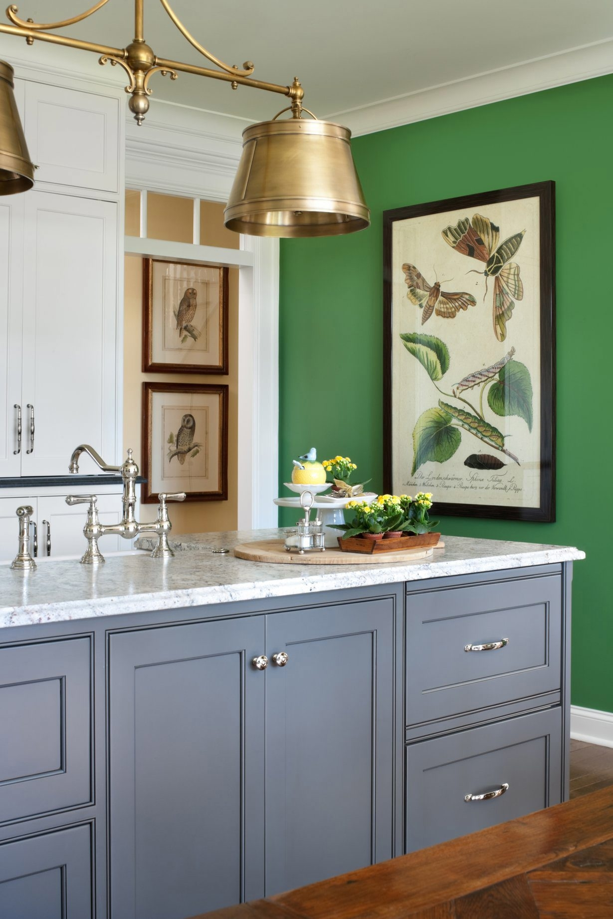 A fresh green wall in the kitchen brings a bit of nature inside. The framed artwork echoes the theme.