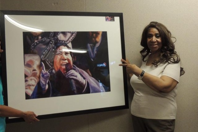 Aretha Franklin poses at Artpark with Jody Ziehm's watercolor painting of her performance during Barack Obama's 2009 inauguration.