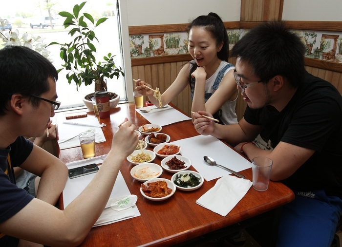 UB students start their meal with the side dishes, or banchan. There are free refills, and the dishes change daily. From left are Arthur Chen, Liliana Guo and Alex Chai. (Photos by Sharon Cantillon/Buffalo News)