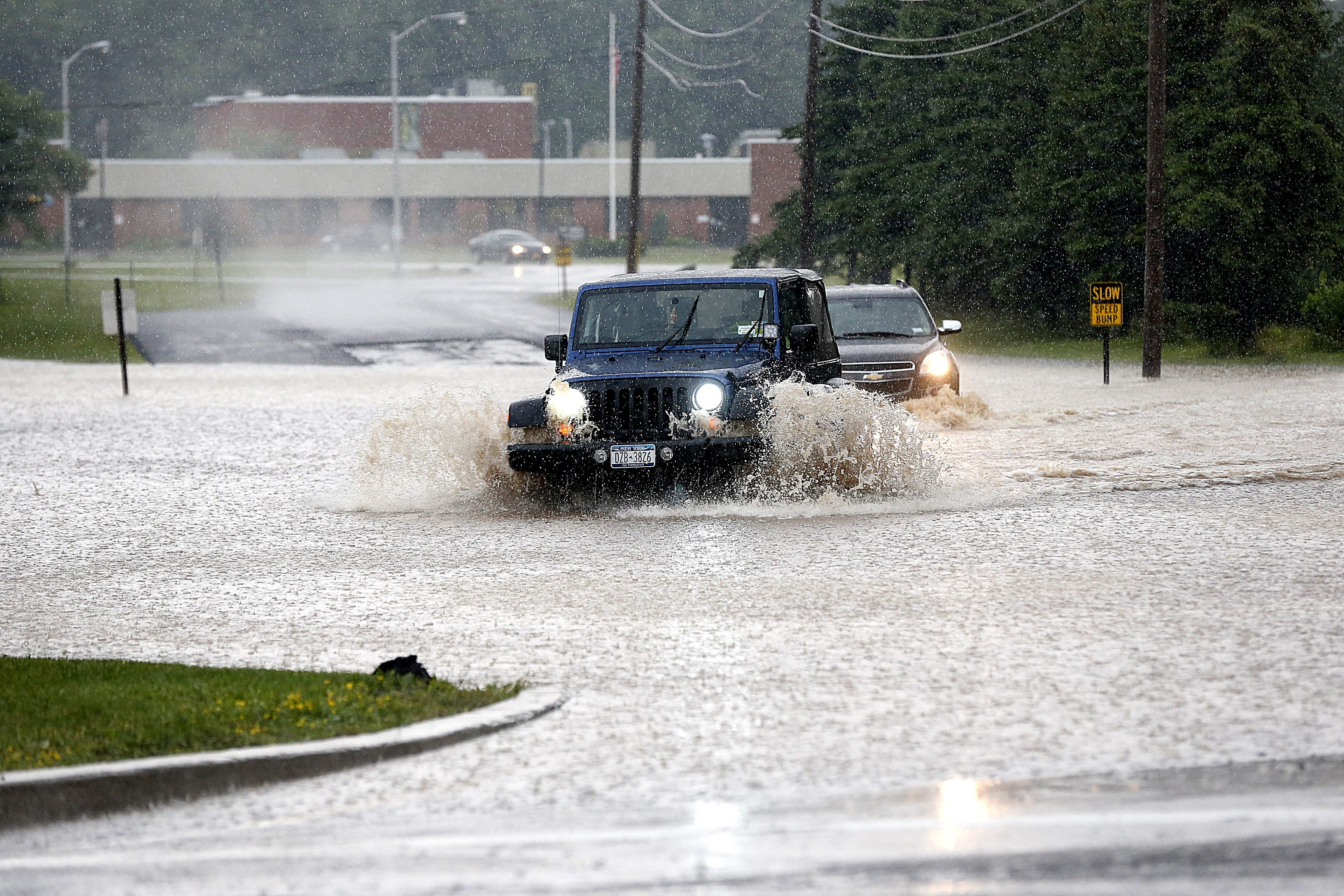 Having trouble finding the road, motorists take their chances negotiating the flooded road outside the Orleans/Niagara BOCES administrative building in Sanborn on Wednesday.