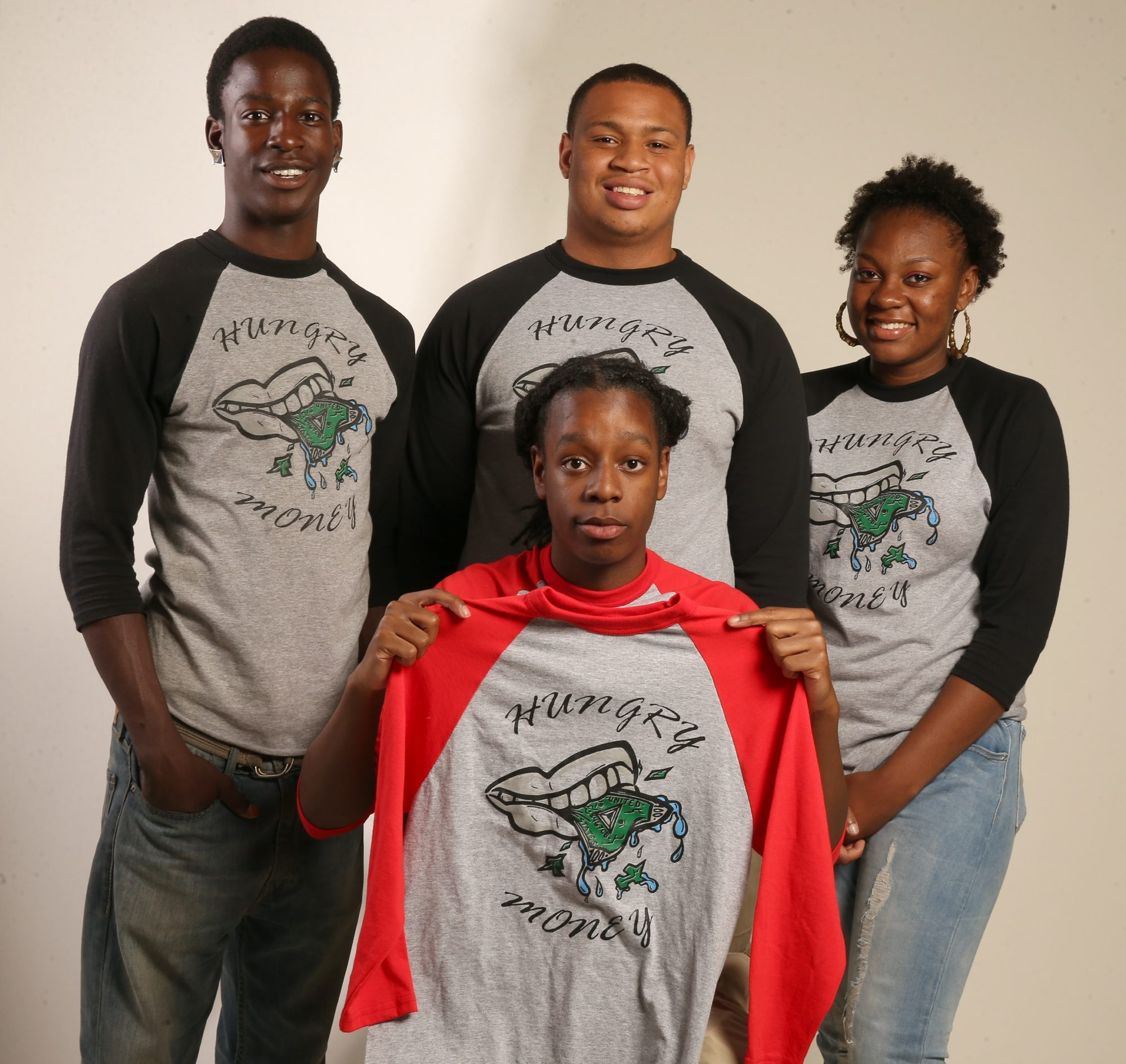 From left, standing, Darius White, Damon Jackson and Hanifah Habeeb, and Damon White, seated, display a T-shirt.