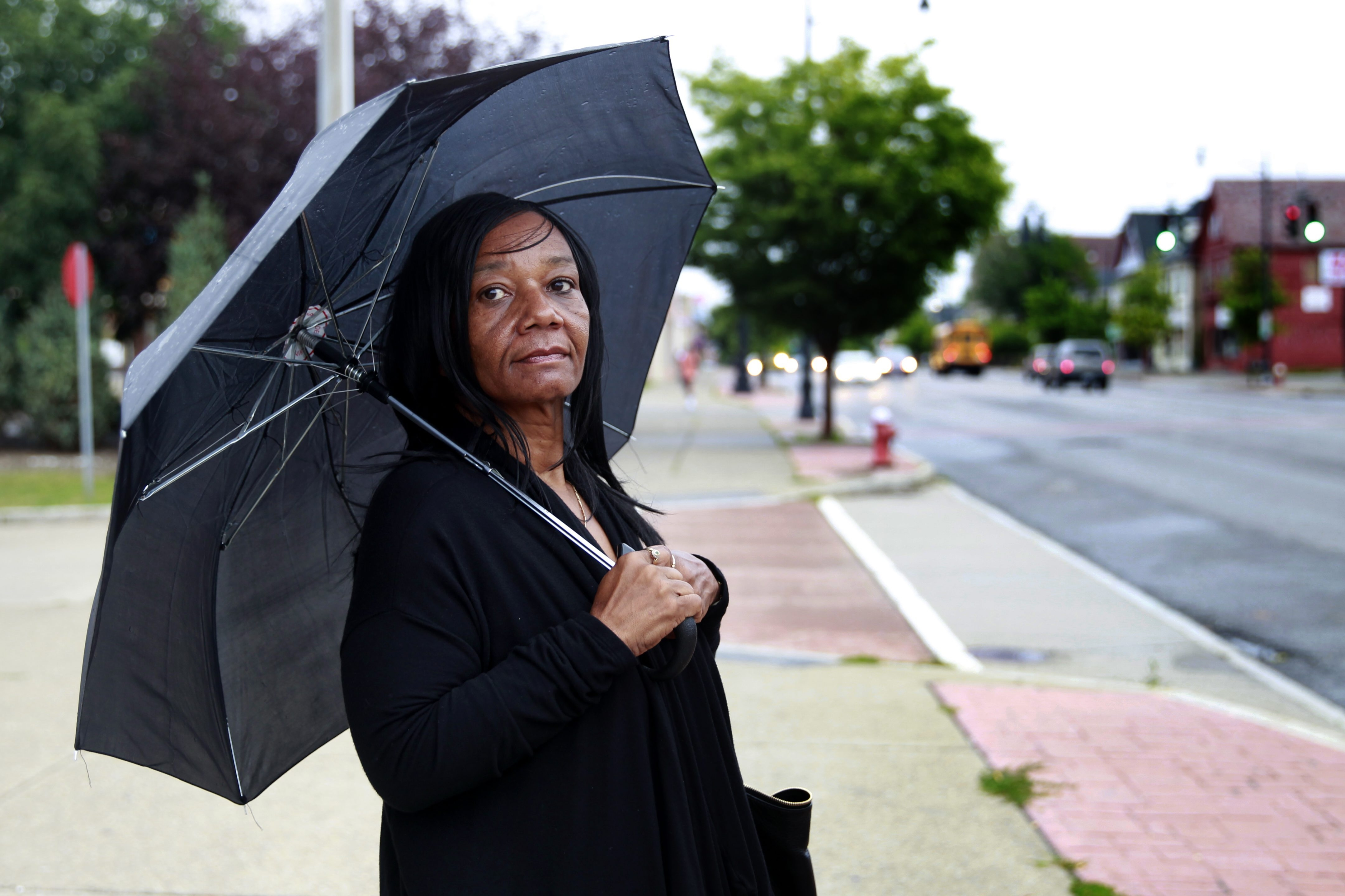 Karen Banks waits for a bus at the corner of Main Street and LaSalle Avenue on Monday as a mist falls.