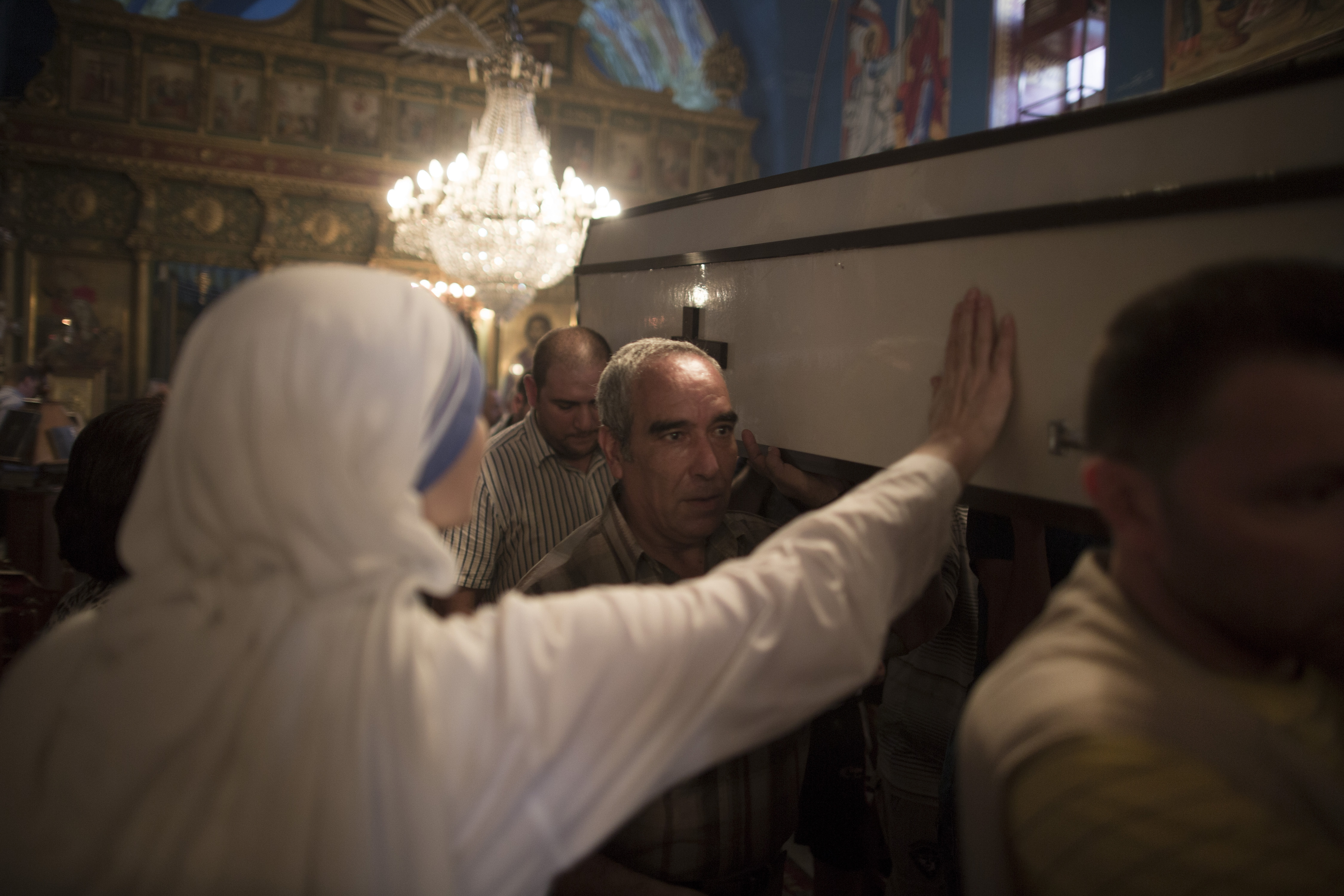 A nun presses her hand to the coffin of Jalila Ayyad, a Christian woman who was killed during an airstrike, at the Church of Saint Porphyrius on Sunday in Gaza City, Gaza Strip. Hamas and Israel went back and forth Sunday over proposals for a humanitarian lull in the Gaza fighting, which has killed more than 1,000 Palestinians and displaced about 200,000.
