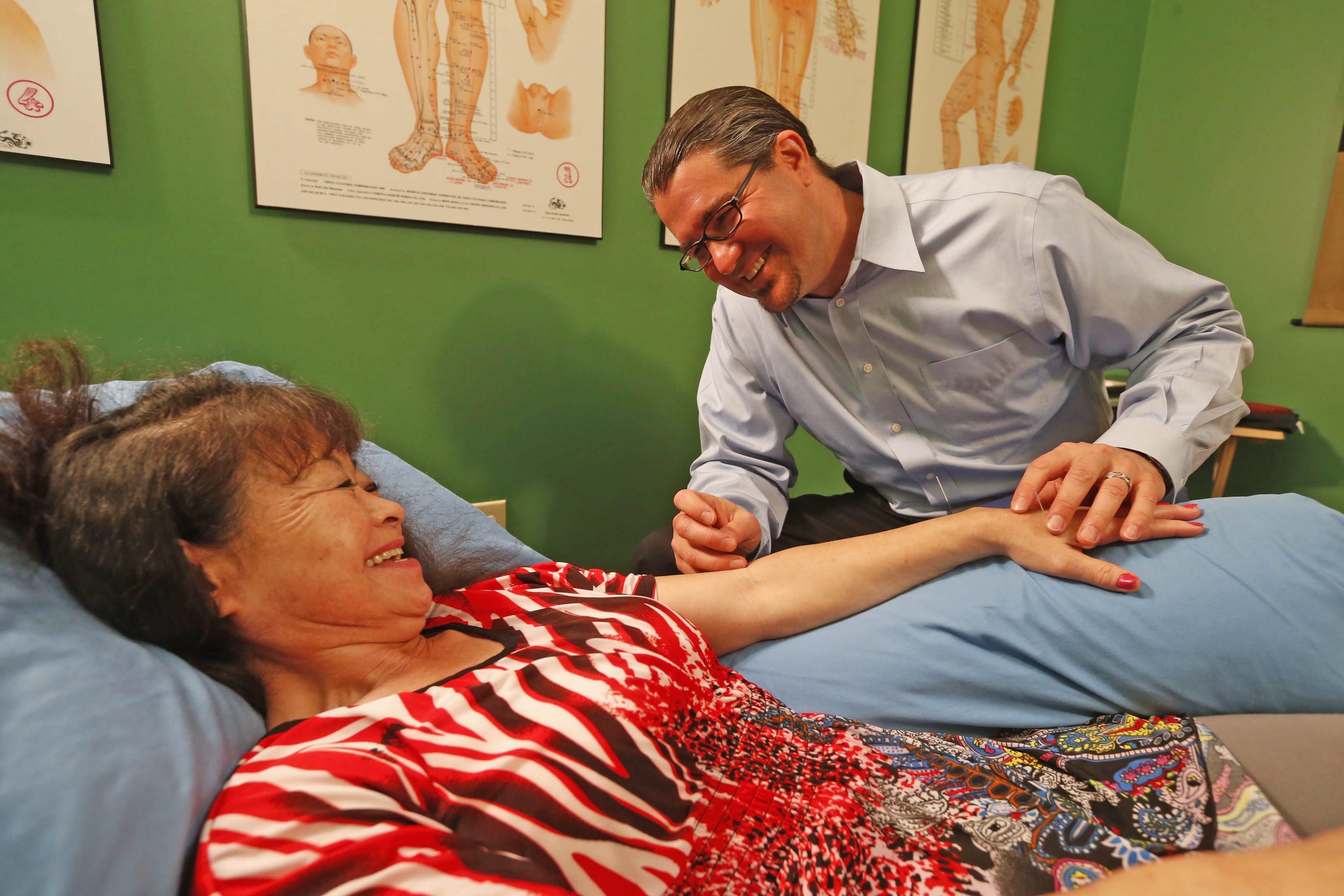 Acupuncturist Destin Radder works with patient Soni Williams, of Getzville, in his Lewiston office July 15. Radder is celebrating his first aniversary in Lewiston.