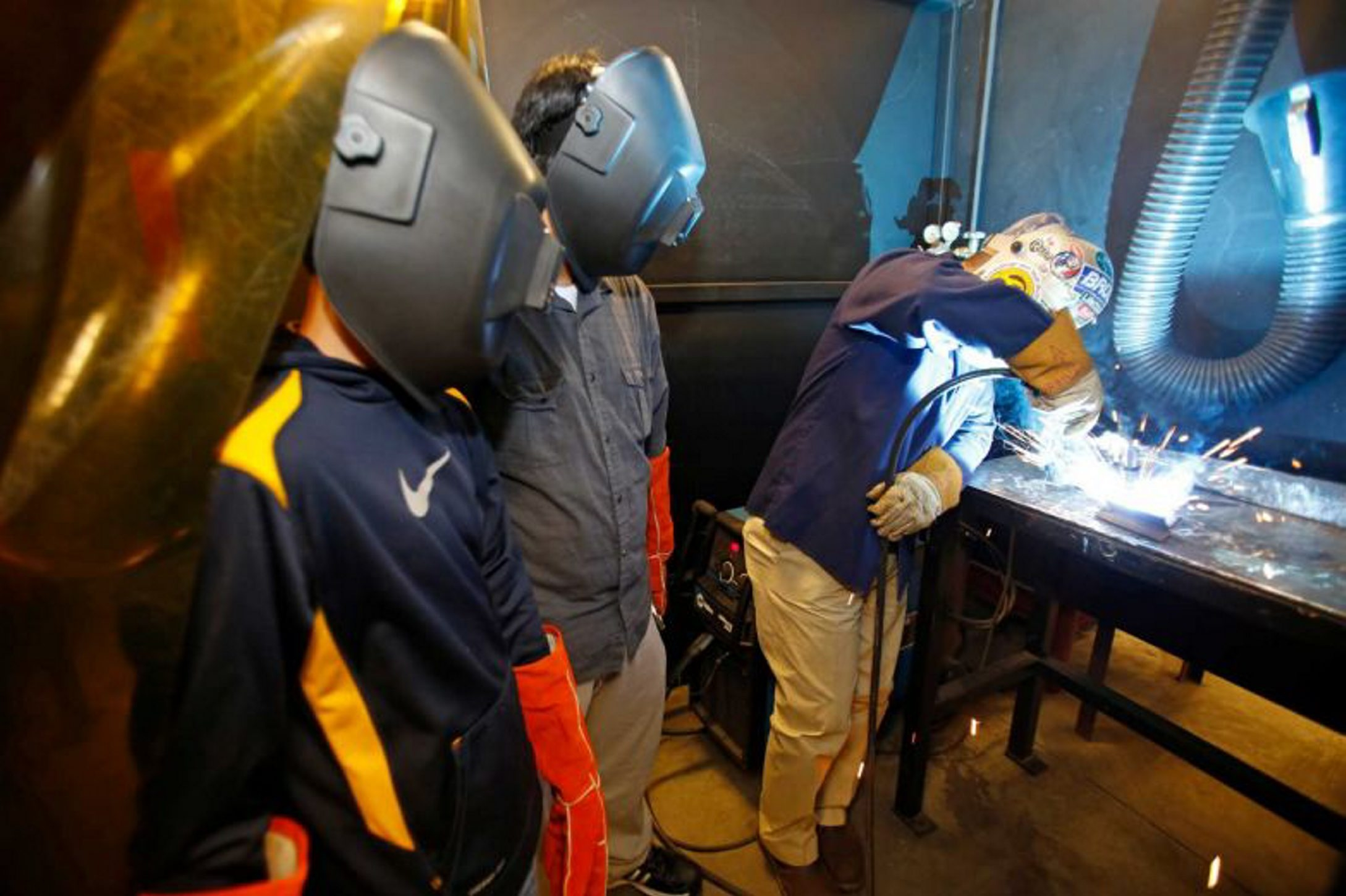 High school students Jose Henner, left, and Alejandro Ibarra watch as Alberto Urbina does a welding demonstration.