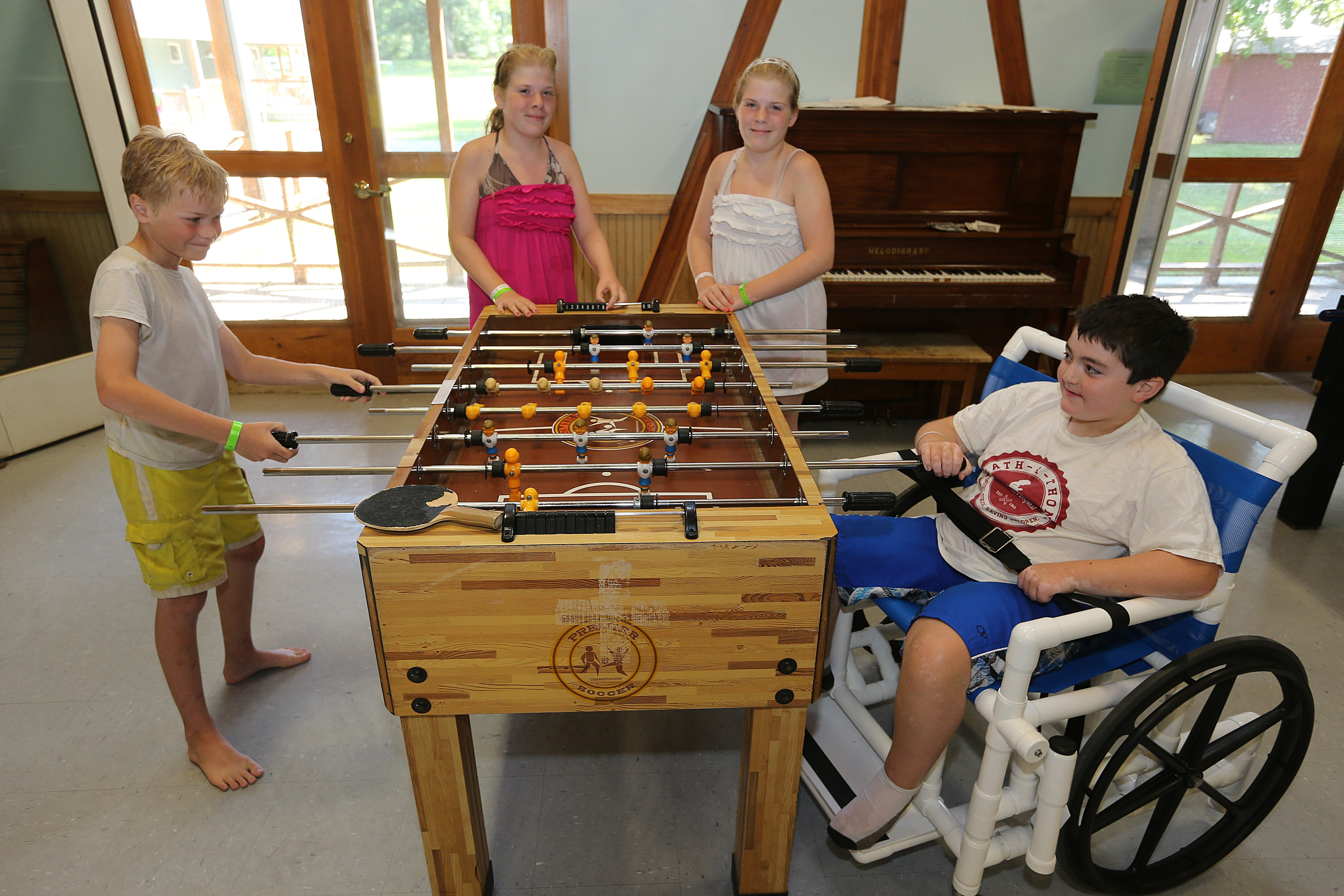 From left: Siblings Cody, 9, Faith and Hope Boone, both 13, of Niagara Falls, and Nathaniel Gavin, 9, of Dunkirk, at the foosball table at Cradle Beach Camp in Angola.