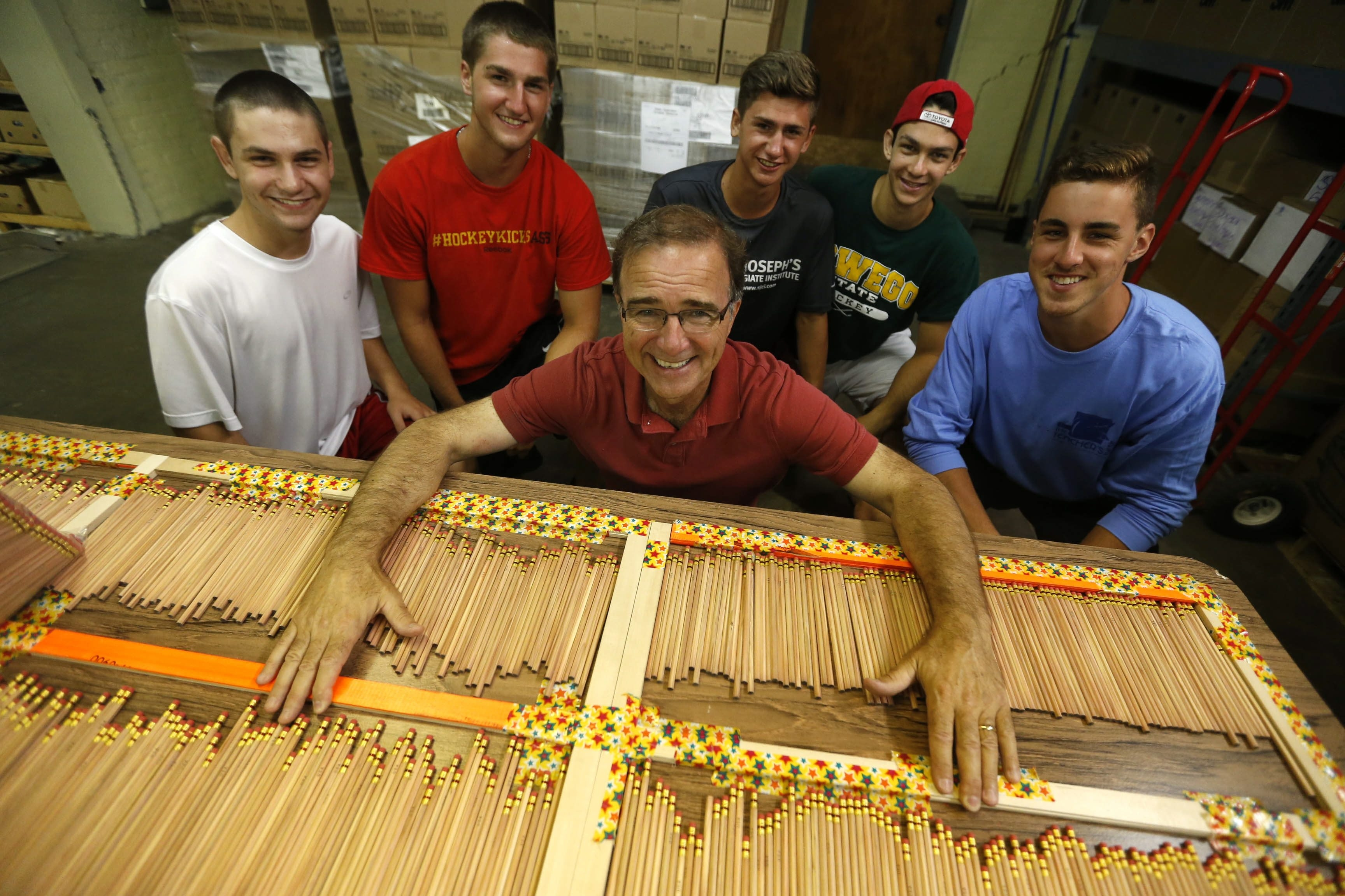 The Pencil Project founder John Mika poses with volunteers next to a small fraction of pencils on a counting table on Wednesday. Mika partnered with First Niagara Bank, Flexo Transparent Inc., NAEIR and Dixon Ticonderoga Co. to obtain the 1 million pencils.
