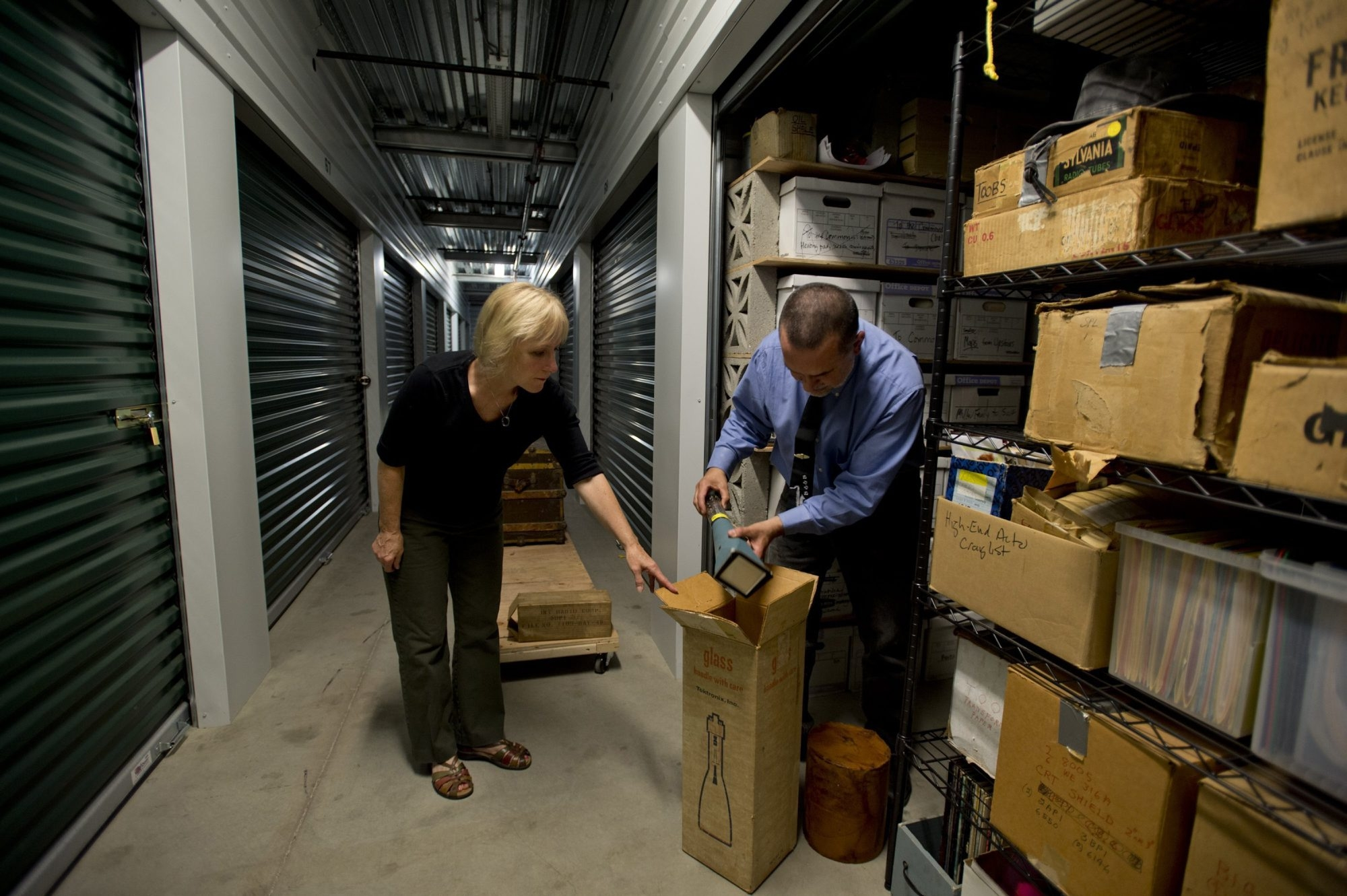 Professional organizer Claudia Smith, left, helps Alan Miller sort through, organize and pare down a storage unit that contains memorabilia once owned by his parents in Davis, Calif.