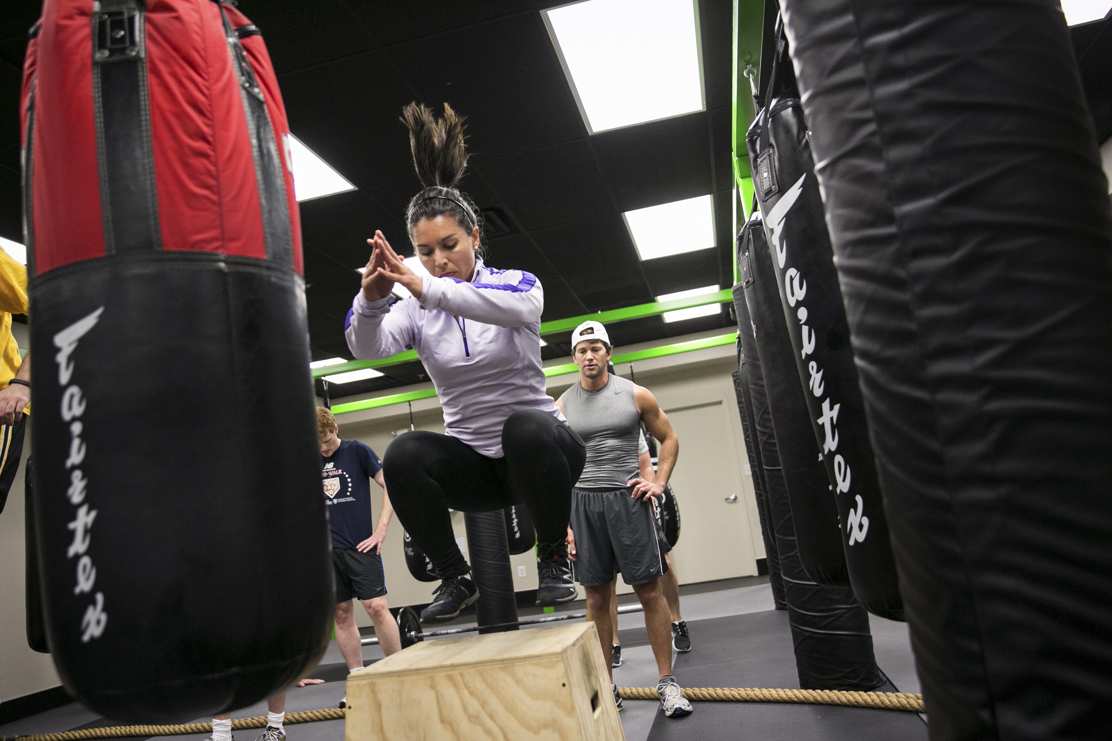Rep. Tulsi Gabbard, D-Hawaii, does a box jump as Rep. Aaron Schock, R-Ill., looks on, at DCBFit Gym in Washington, D.C., during an intense workout routine led by Rep. Markwayne Mullin, R-Okla.