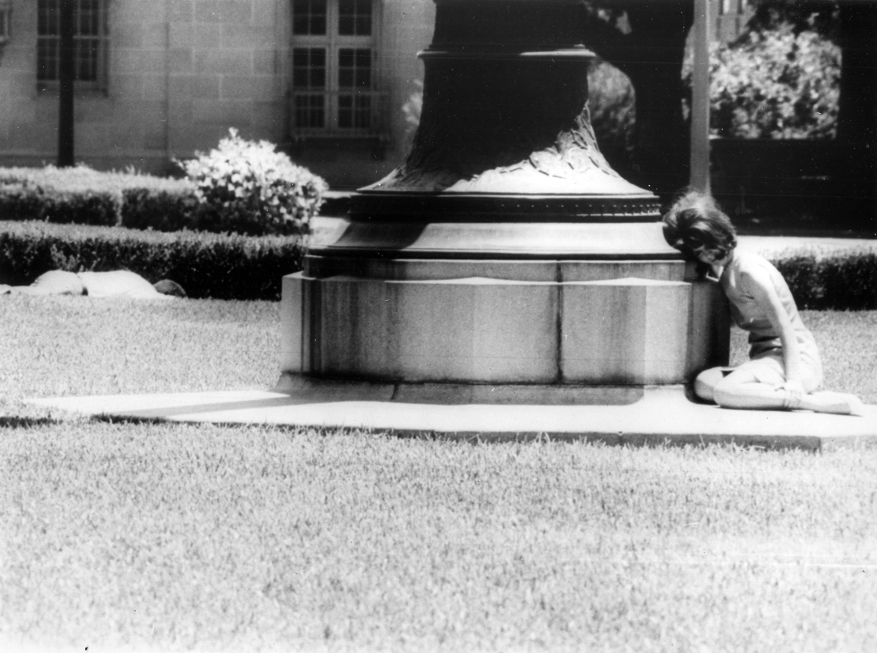 This dramatic photo of a young woman hiding behind a statue as a man lay wounded nearby was taken by a United Press International photographer as Charles Whitman was still firing.
