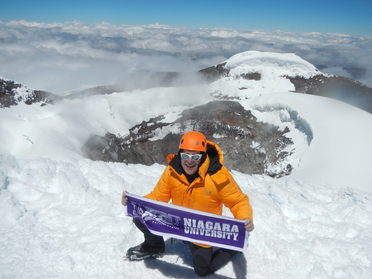 It's a happy, albeit unconventional, Fourth of July for Ed Hutton, Niagara University finance professor, who brings a school banner to an elevation of 18,000 feet on Cotopaxi in the Andes of Ecuador, one of the highest active volcanoes in the world. He helps raise money for his NU student project by finding sponsors for his climbs and also meets with prospective partners.