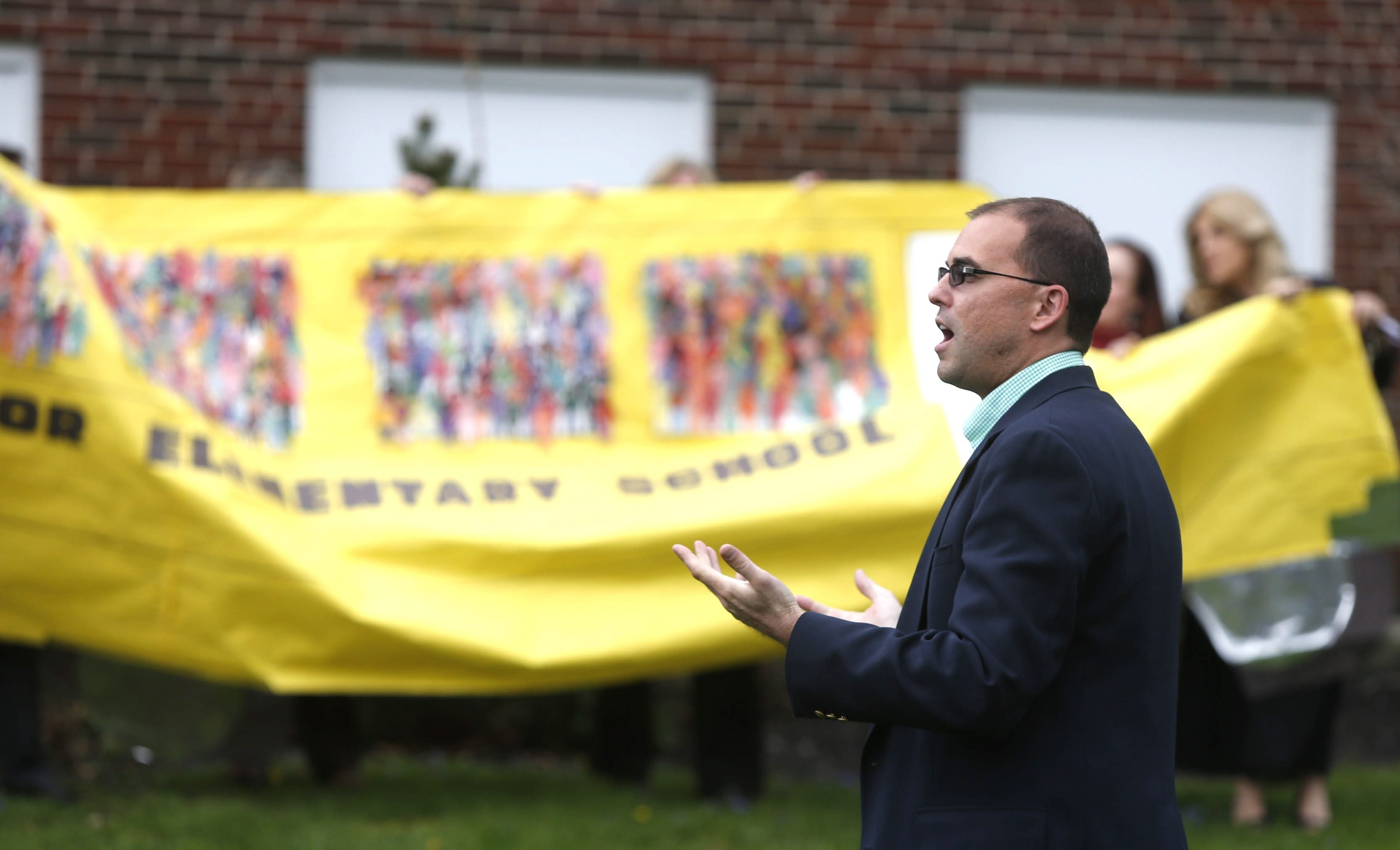 """Richard Jetter thanks those in attendance for their support at a rally May 7 held after the Hamburg superintendent reported his car had been vandalized during a school board meeting. The yellow energy bus sign held by members of the community in the photo from the rally refers to a book, """"The Energy Bus,"""" something Jetter liked to quote.  (Robert Kirkham/Buffalo News)"""