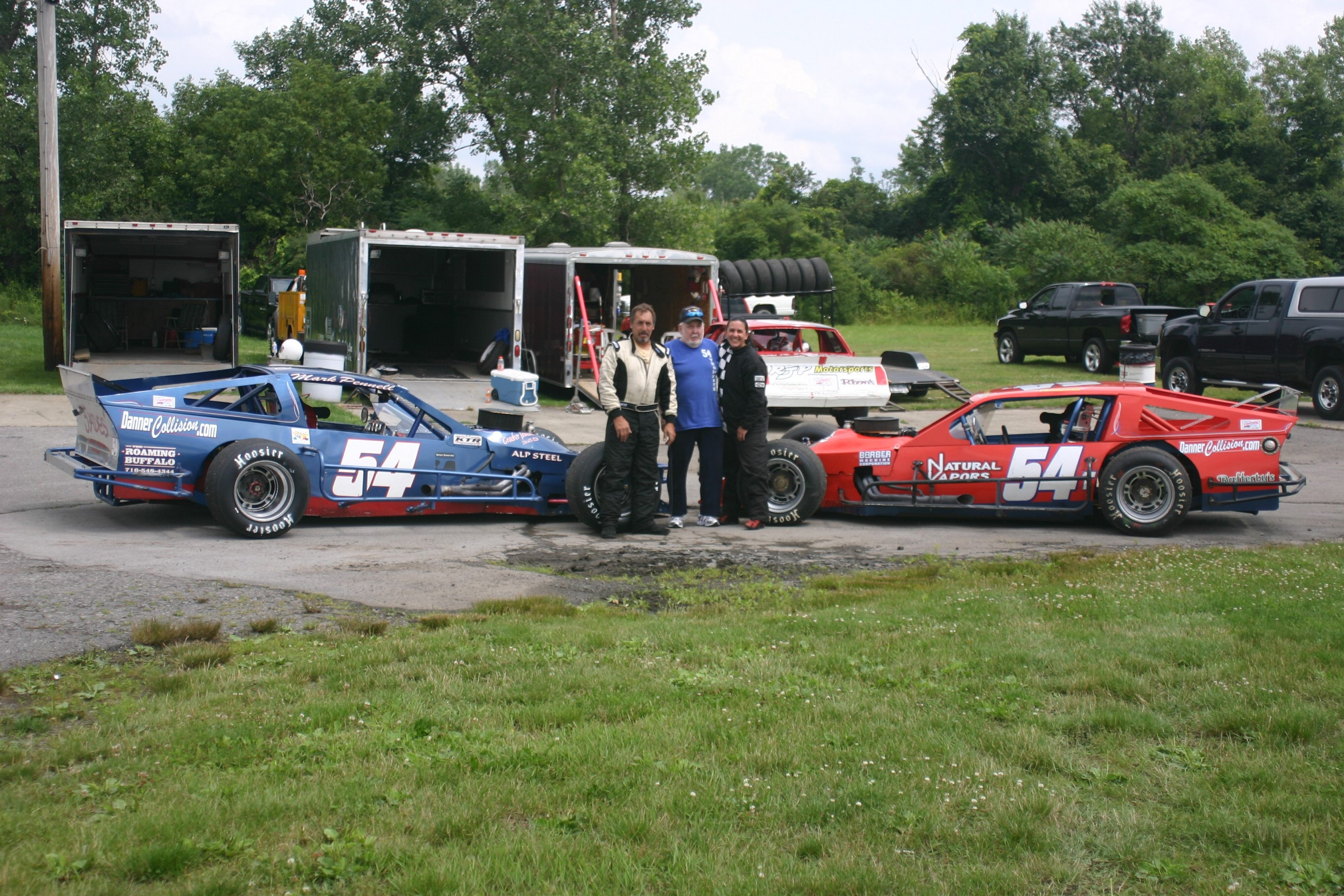 Driver Mark Pennell, left, owner Jim Thompson, center, and driver Jayme Thompson with the team's two  Sportman Division cars.