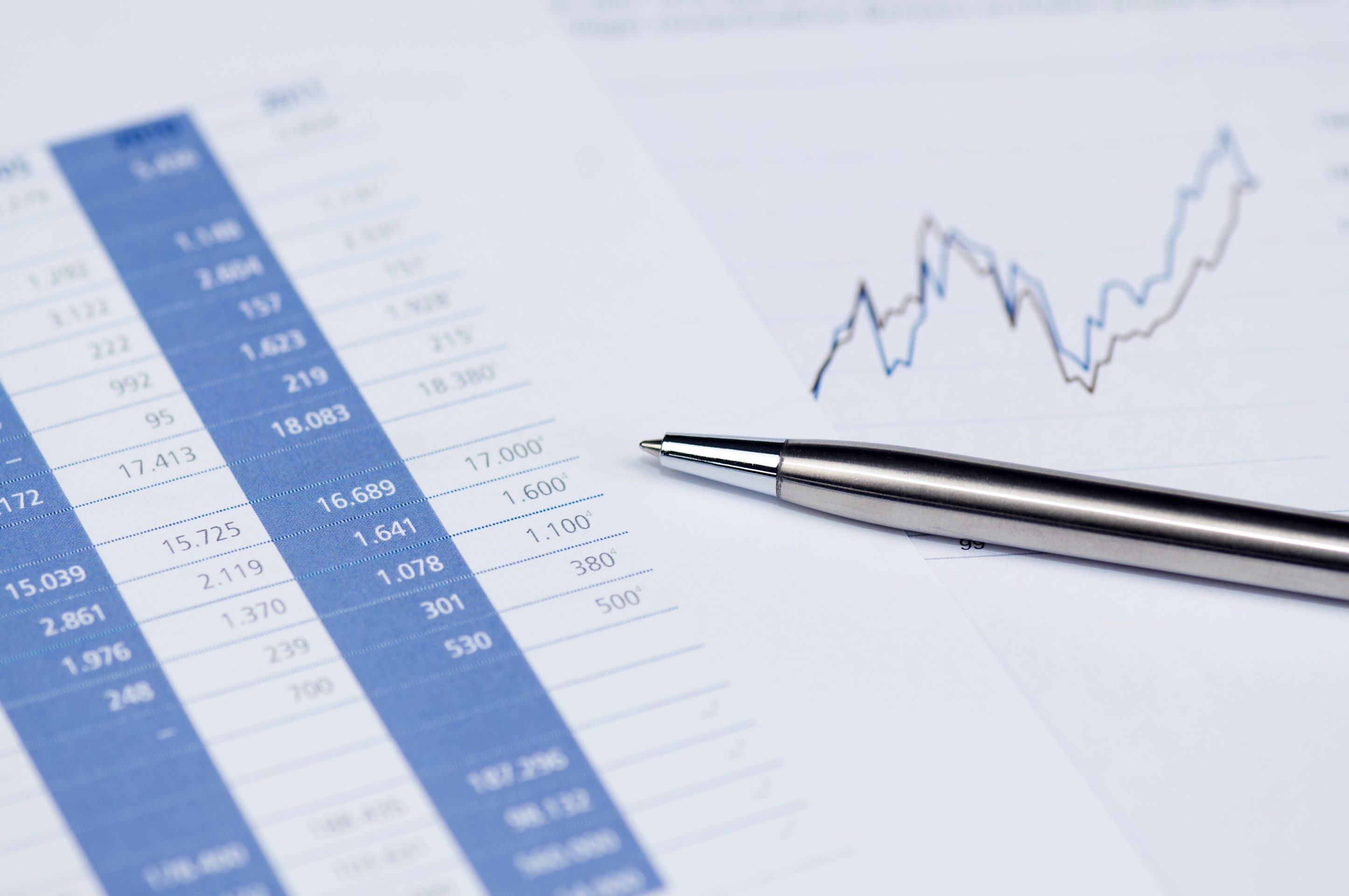 Business concept – Financial planning with stock chart and pen, toned image.