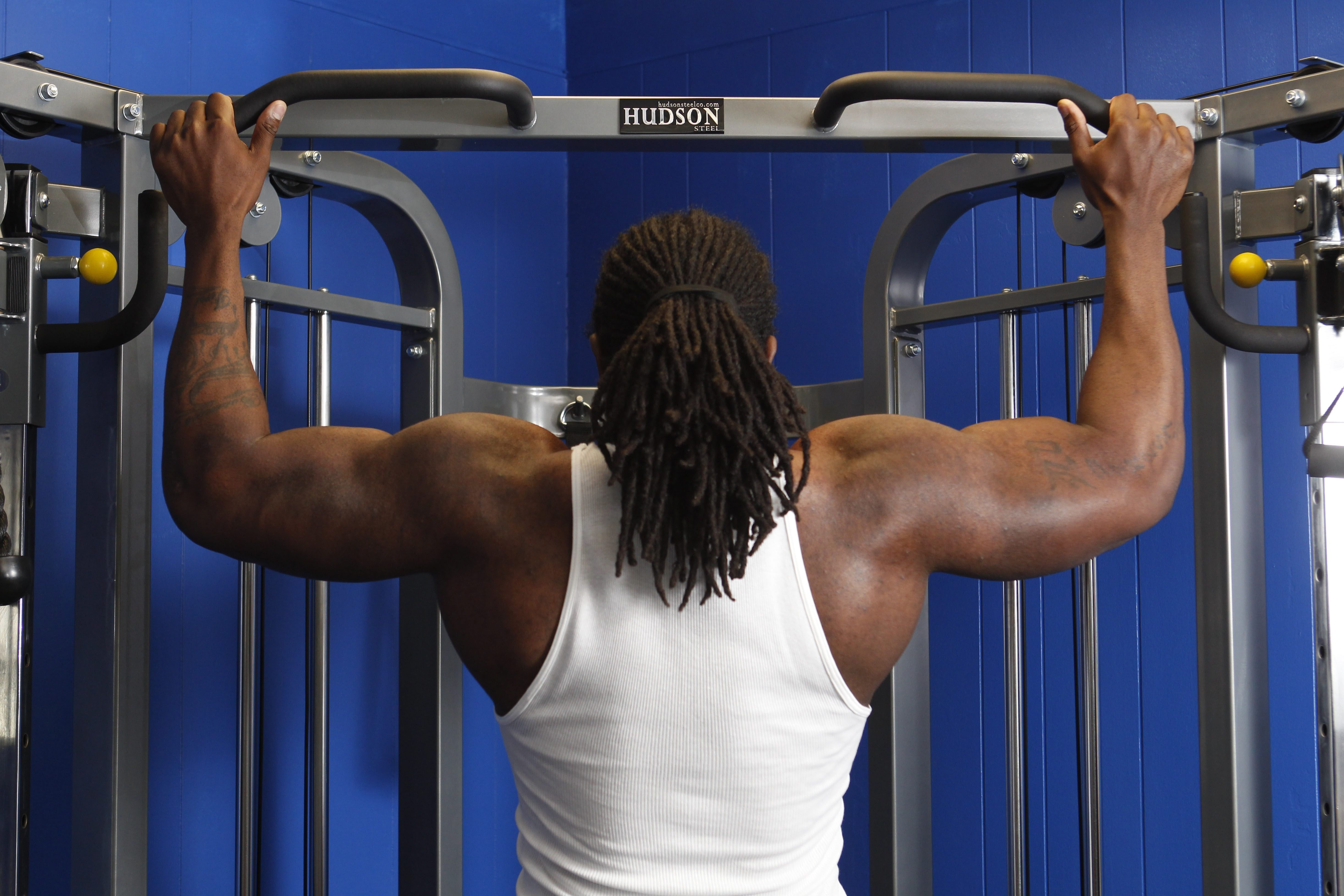 Dwayne Brinson is a personal fitness trainer and the owner of Fit Nation which recently opened on Main Street in Williamsville.  He works out six days a week. He does wide-grip pull-ups, June, 10, 2014. (Sharon Cantillon/Buffalo News)