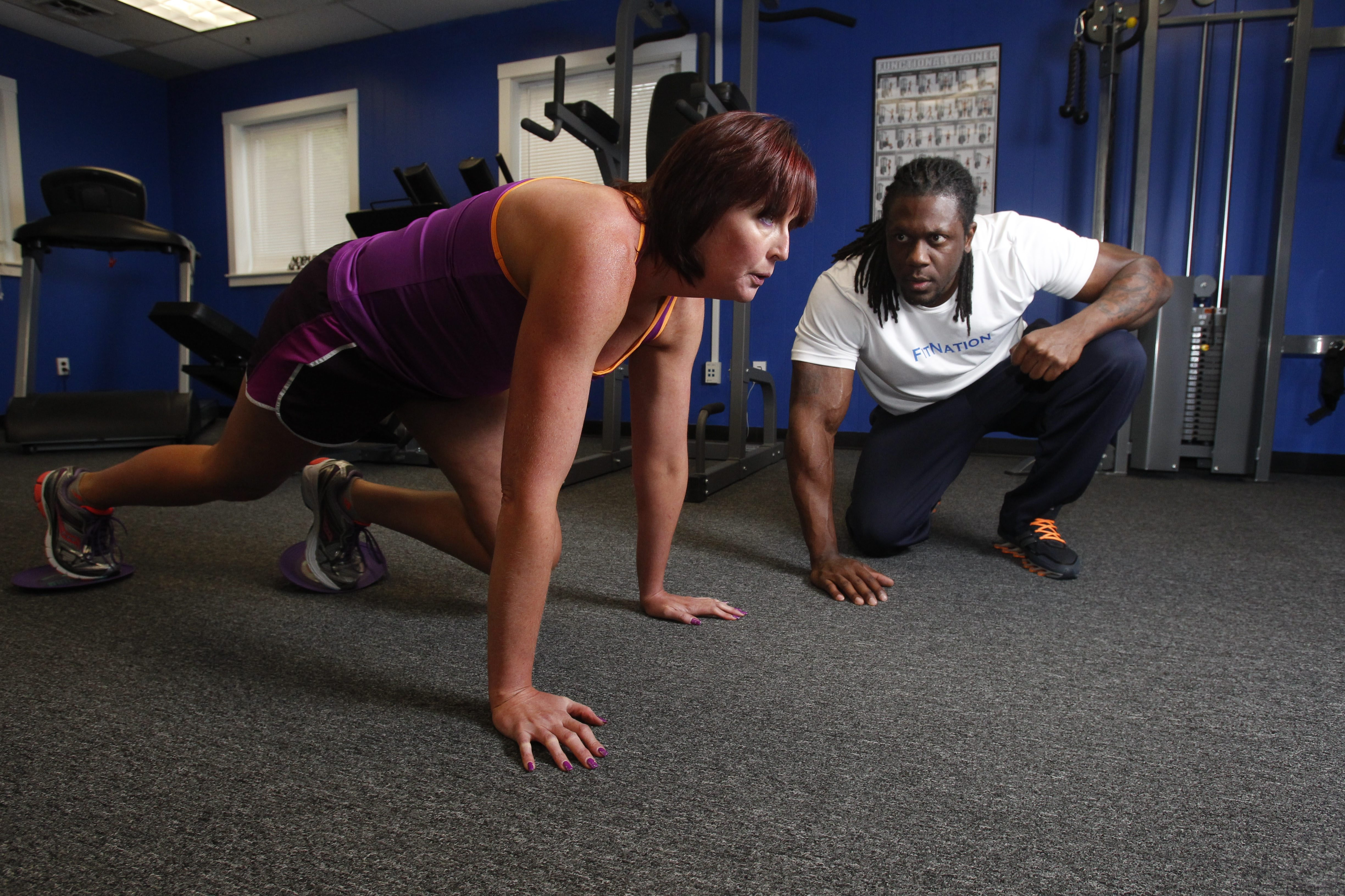 """""""I don't necessarily want to be a bodybuilder, but I wanted that look,"""" said Jennifer Gruber, shown working out with Dwayne Brinson, who helped her lose nearly 65 pounds."""