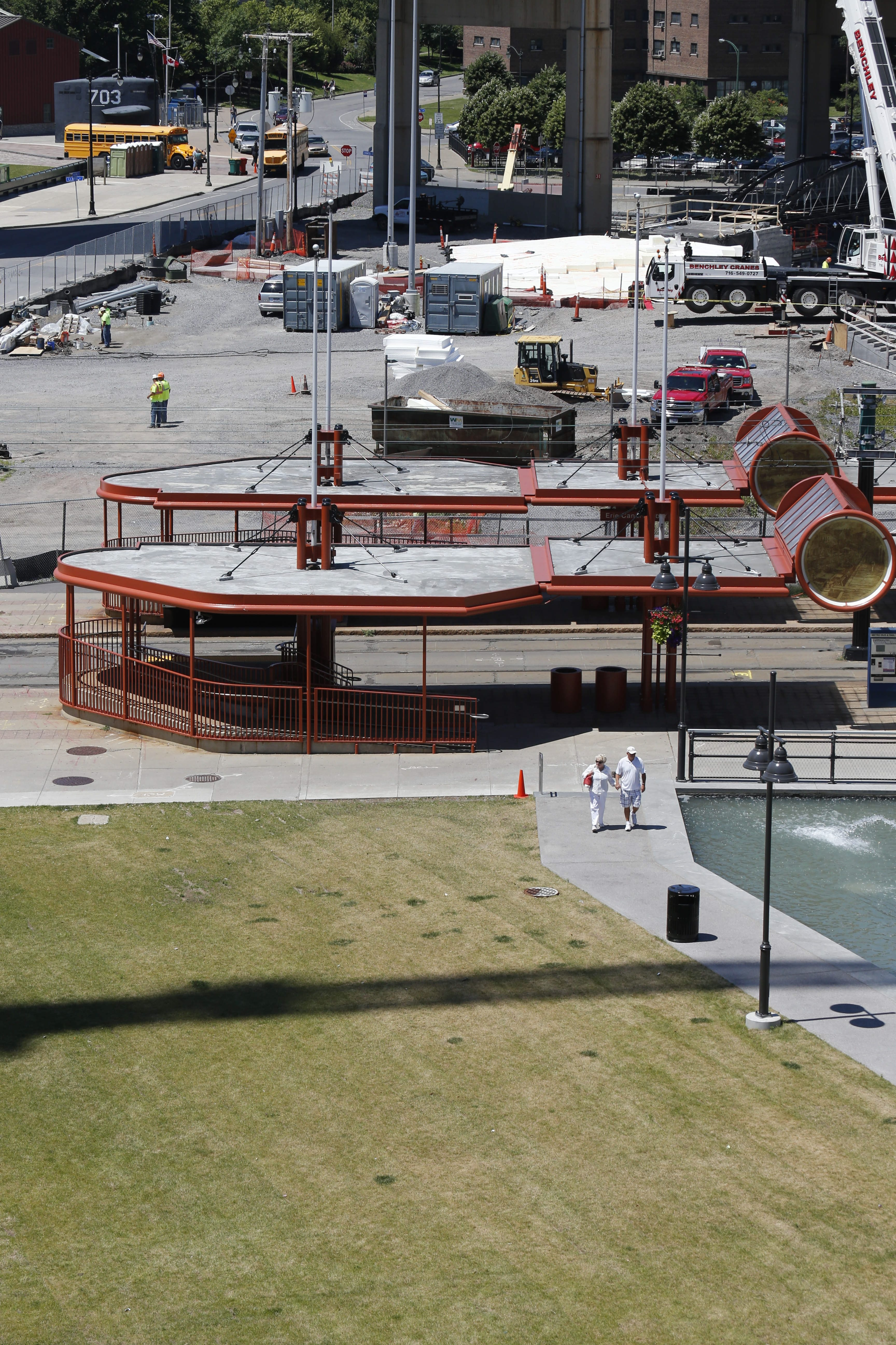 Construction continues at the site of the former Memorial Auditorium at Canalside on Thursday. The second of three bridges that will span the canals was delivered to the site in seven parts.