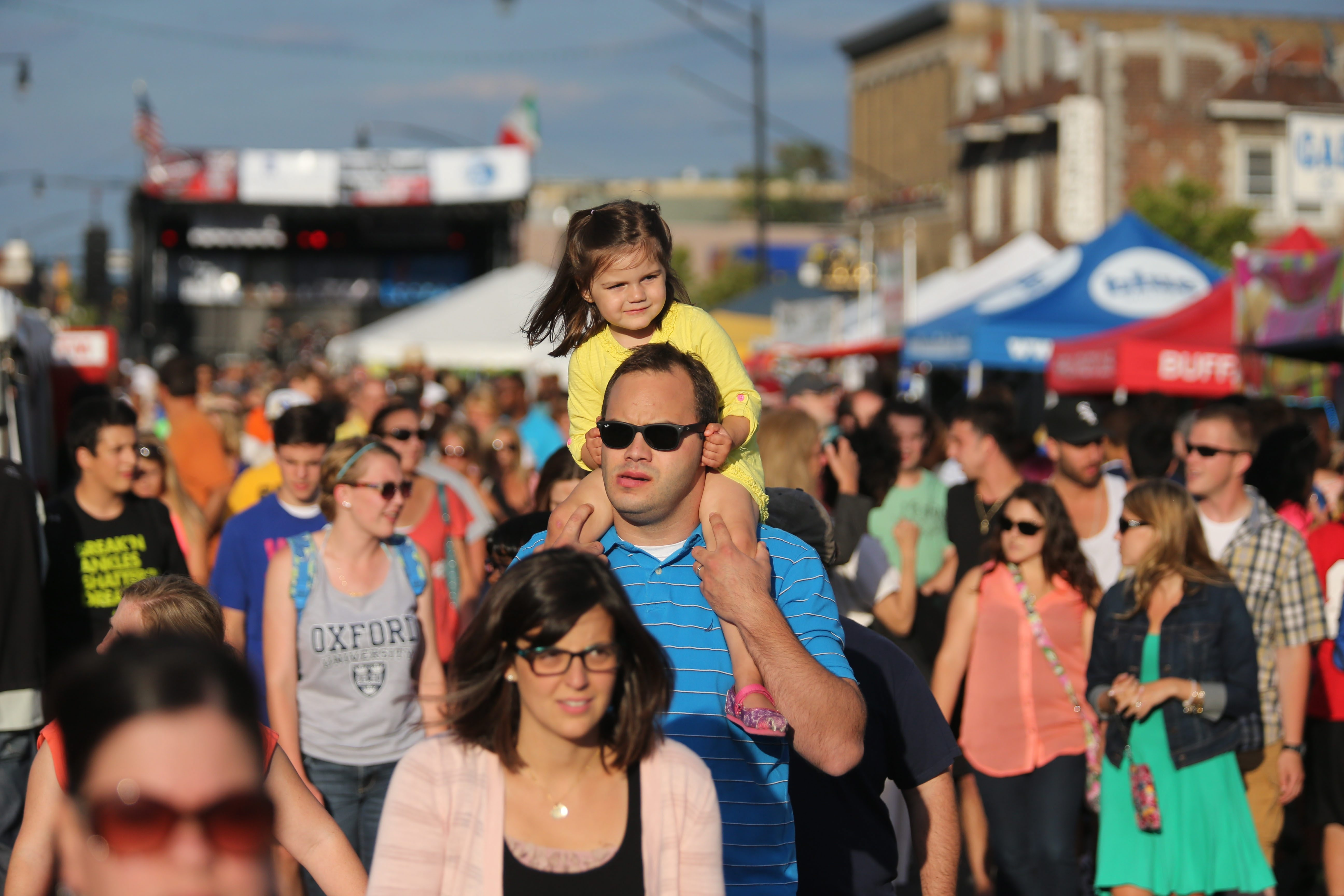 Mark Shepard, of Buffalo, carries his daughter Nora, 3, on his shoulders, along Hertel Avenue on Thursday, the first day of the Italian Heritage Festival on Hertel Avenue.